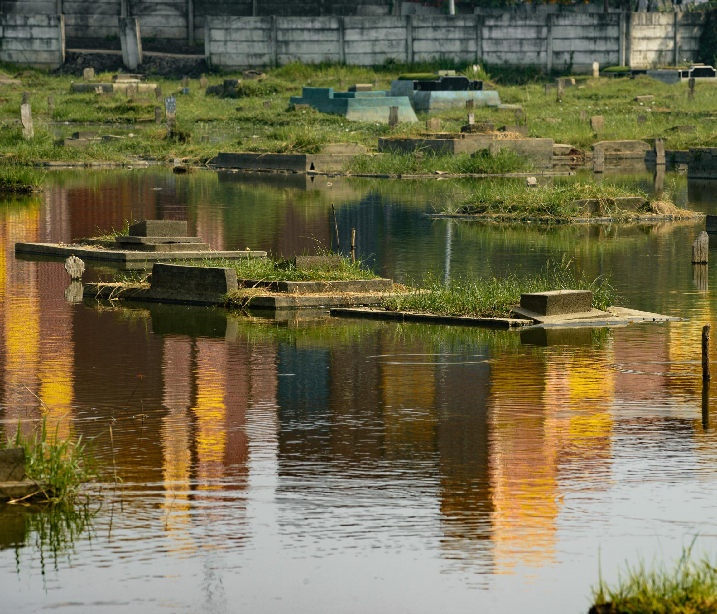 Refleksi tumpukan peti kemas di seberang TPU Semper yang terendam genangan air