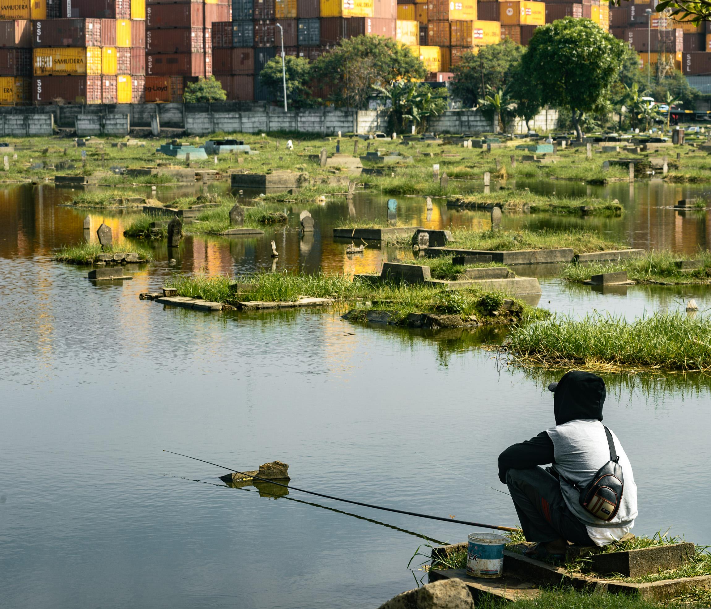 Warga memancing ikan di genangan air TPU Semper