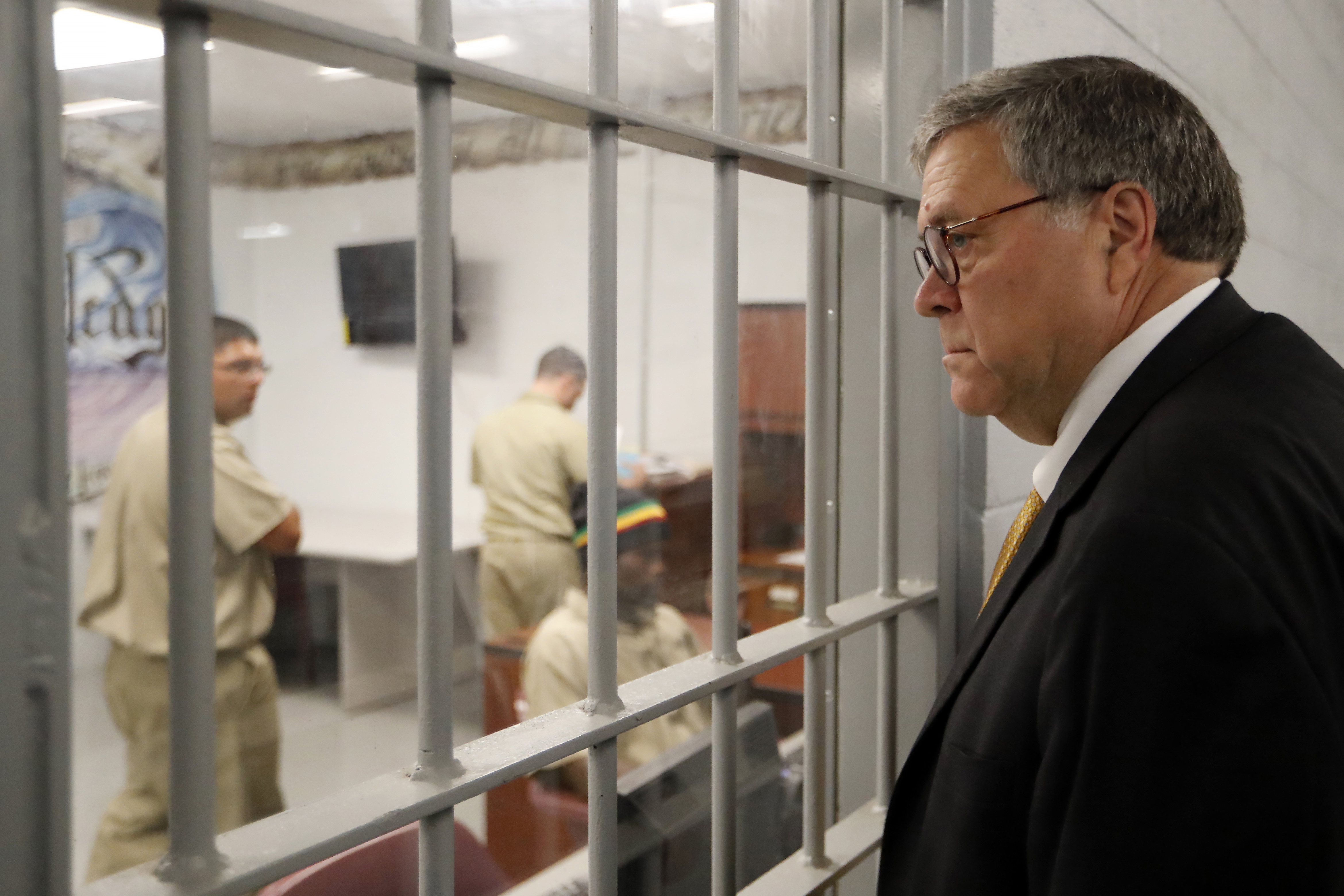 Attorney General William Barr watches as inmates work in a computer class during a tour of a federal prison in Edgefield, S.C. on July 8, 2019.