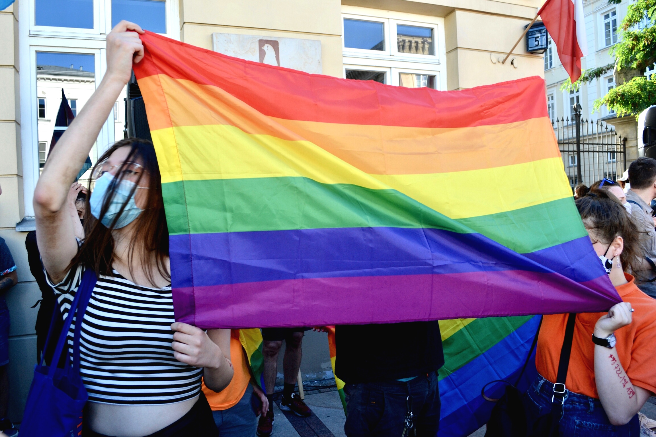 A rainbow flag is held up at a counter protests.