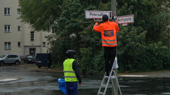 Rocco und seine Brüder. Two men in high visibility vests taking down a street sign.