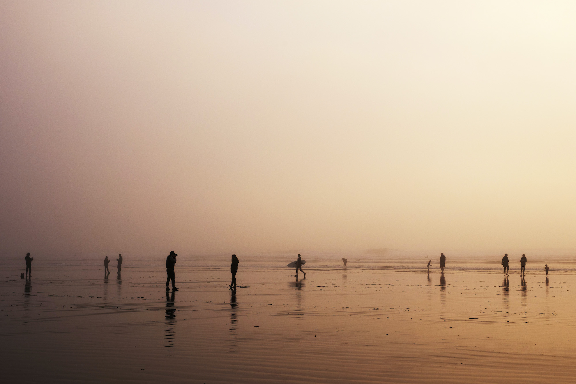 People walk along Cox Bay Beach in Tofino at sunset