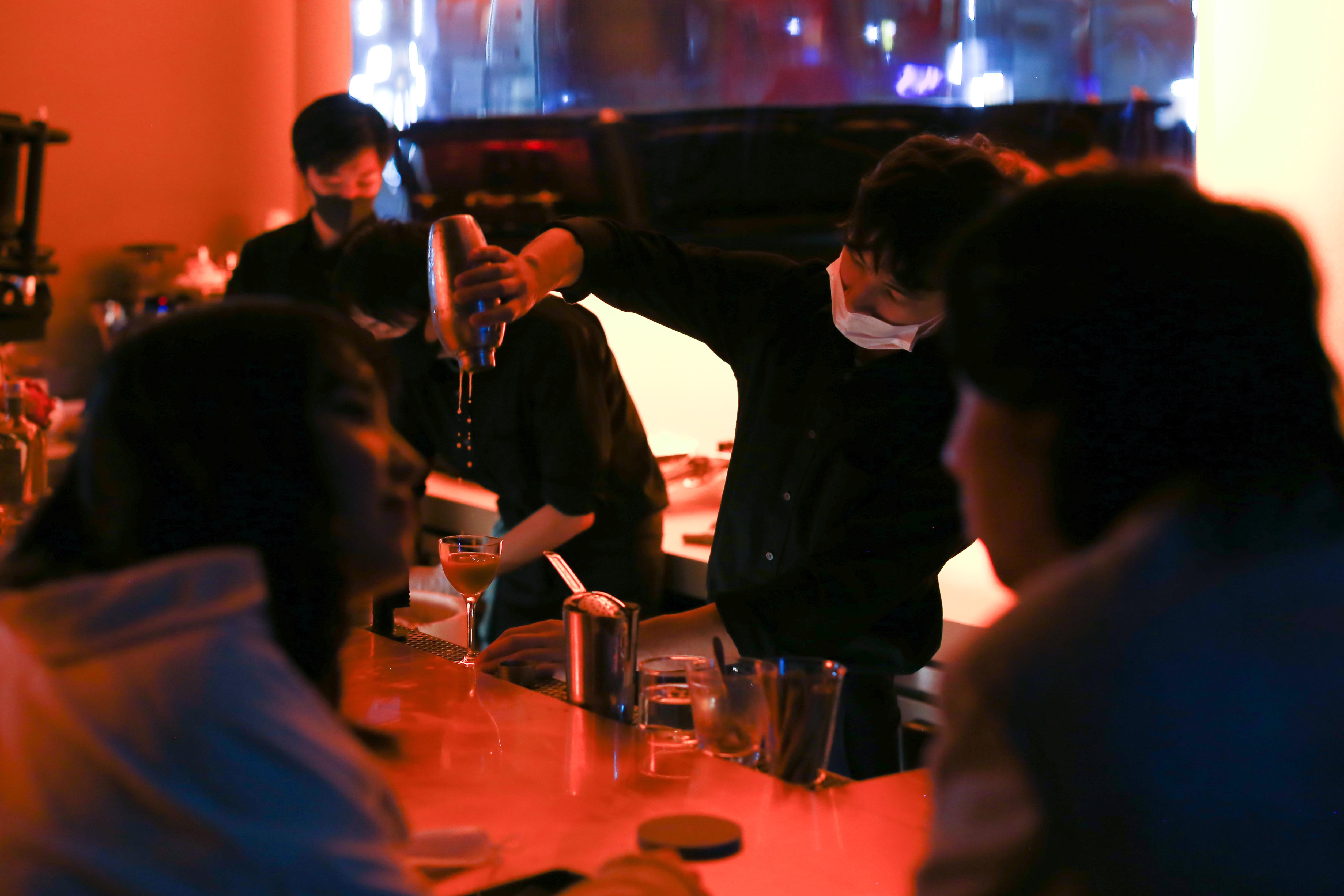 Seorang bartender menuangkan minuman
