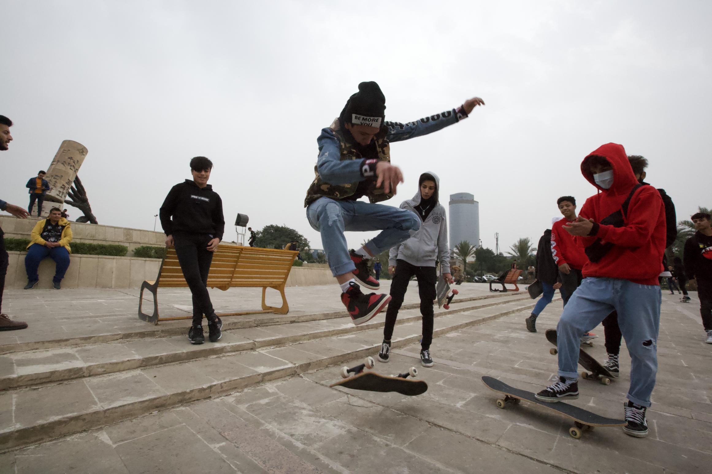 Seorang skater melakukan trik di depan teman-temannya.