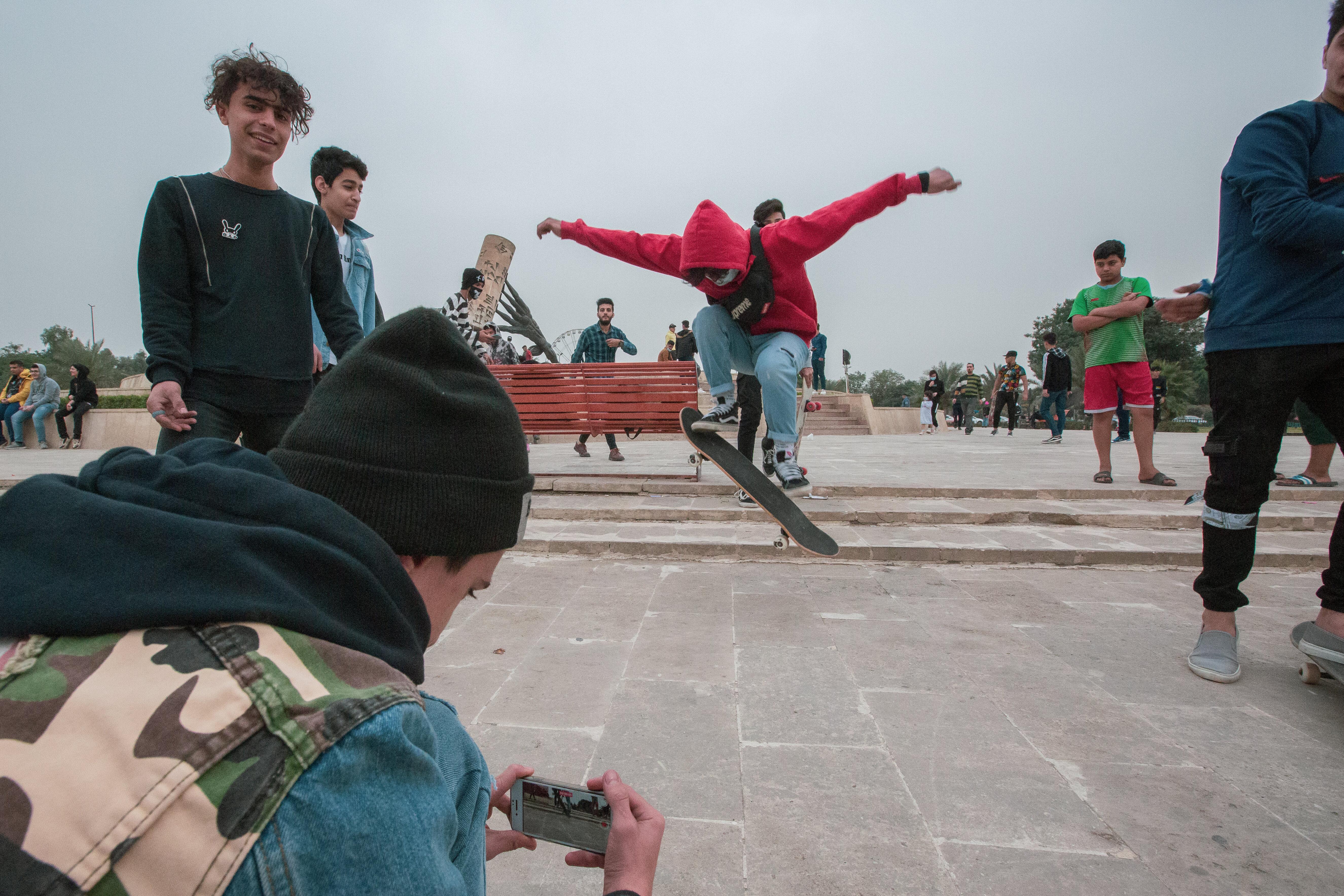 Seorang skater memamerkan trik sambil direkam temannya.