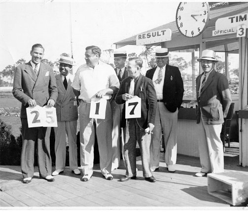 Baseball greats and racing fans: (front, L to R) Dizzy Dean, Babe Ruth, and Rabbit Maranville hold numbers that were hand placed on the odds board. Behind are the three judges Sid Harris, Tom and Heuse Gregory and odds board number placer.