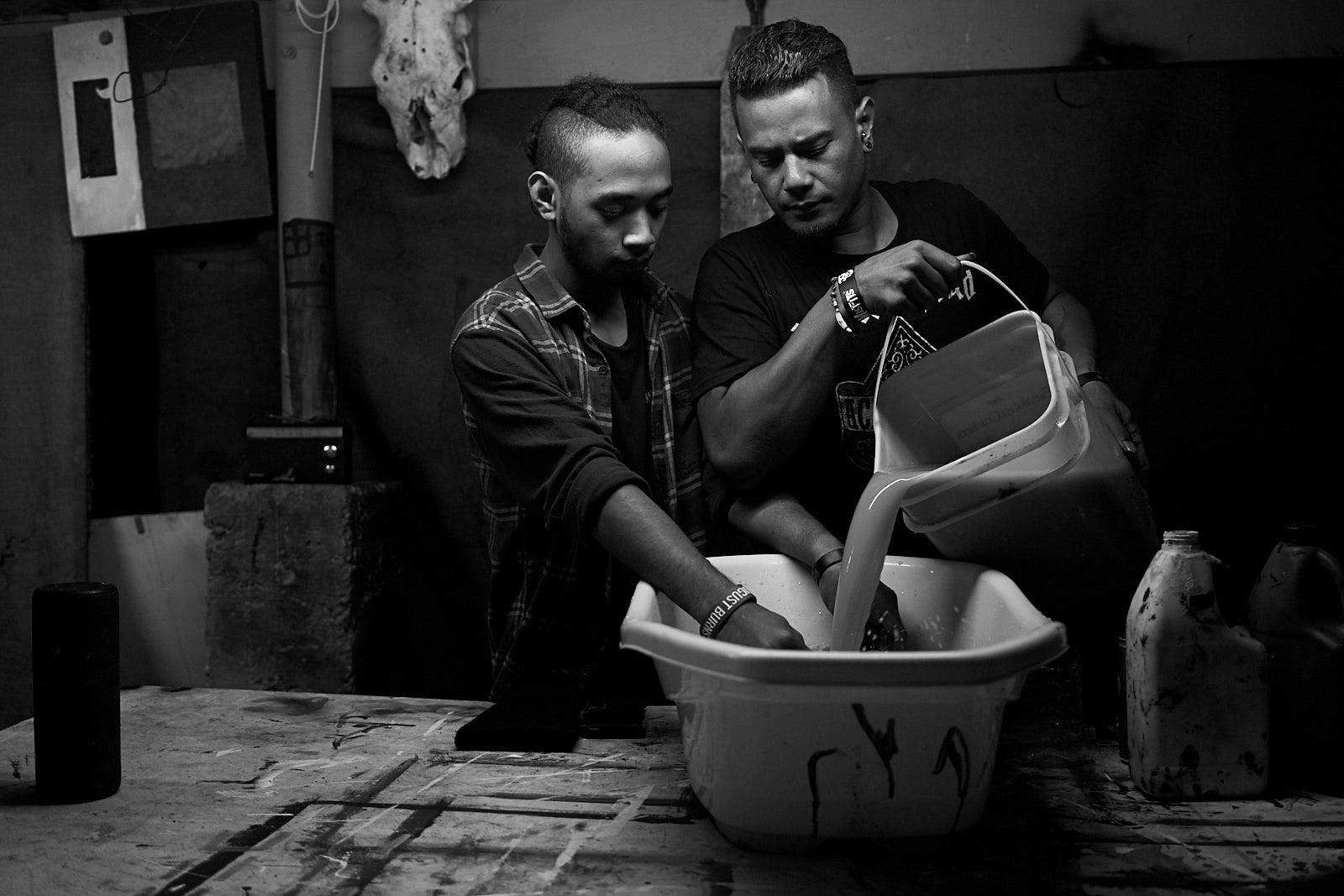 Dua laki-laki menuang cairan ke dalam baskom