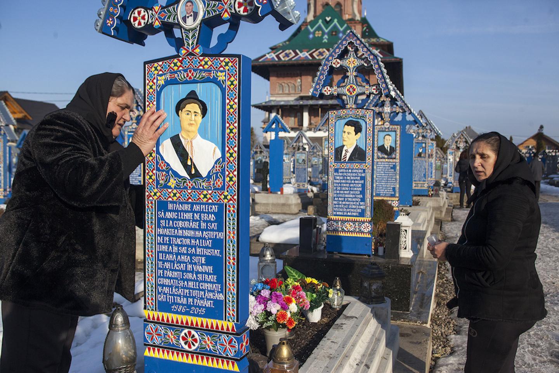 Dua perempuan berdiri di samping deretan makam
