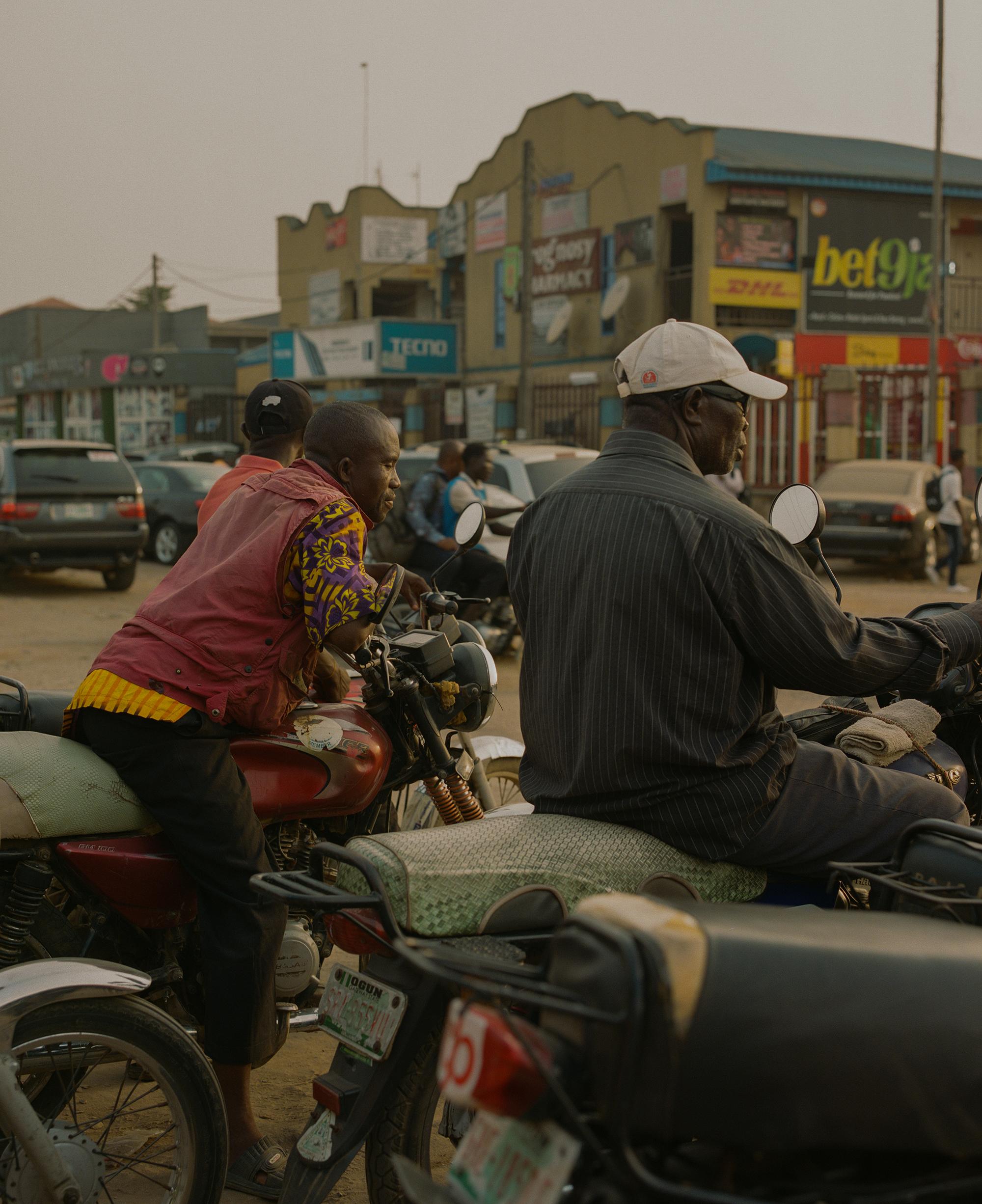 dua lelaki duduk di atas motor masing-masing