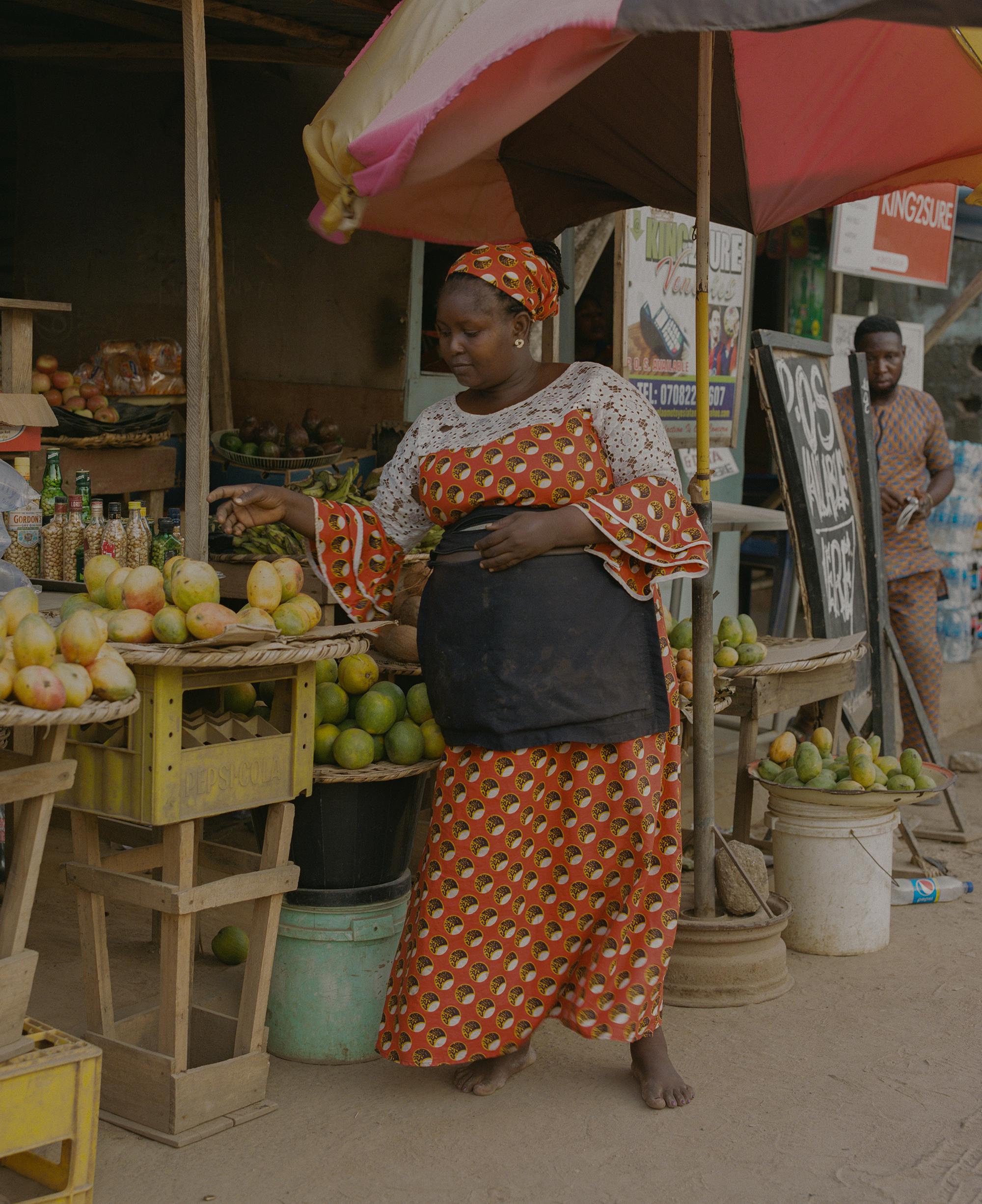 Ibu-ibu tampak ingin mengambil buah yang dijajakan di warung