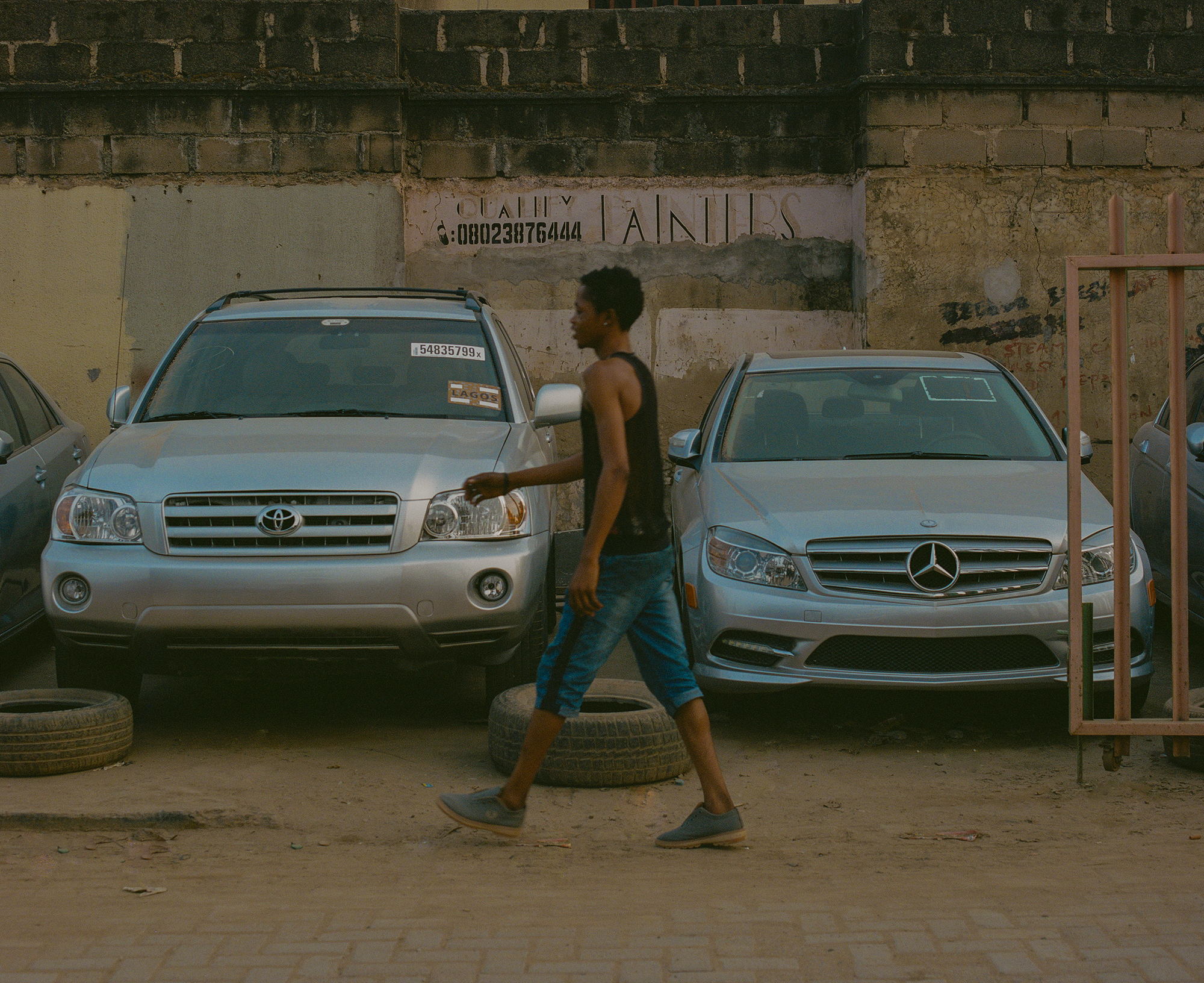 Lelaki berjalan di depan barisan mobil