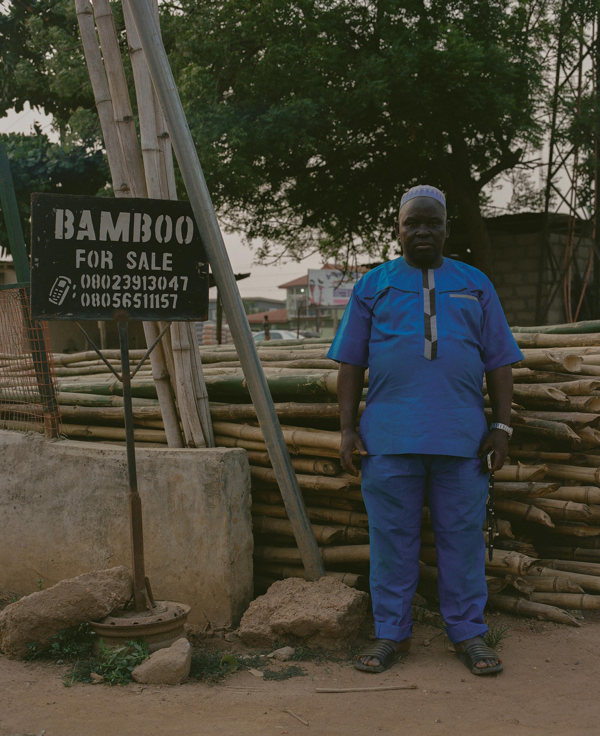 Lelaki berpakaian serba biru berpose di tempat jualan bambu