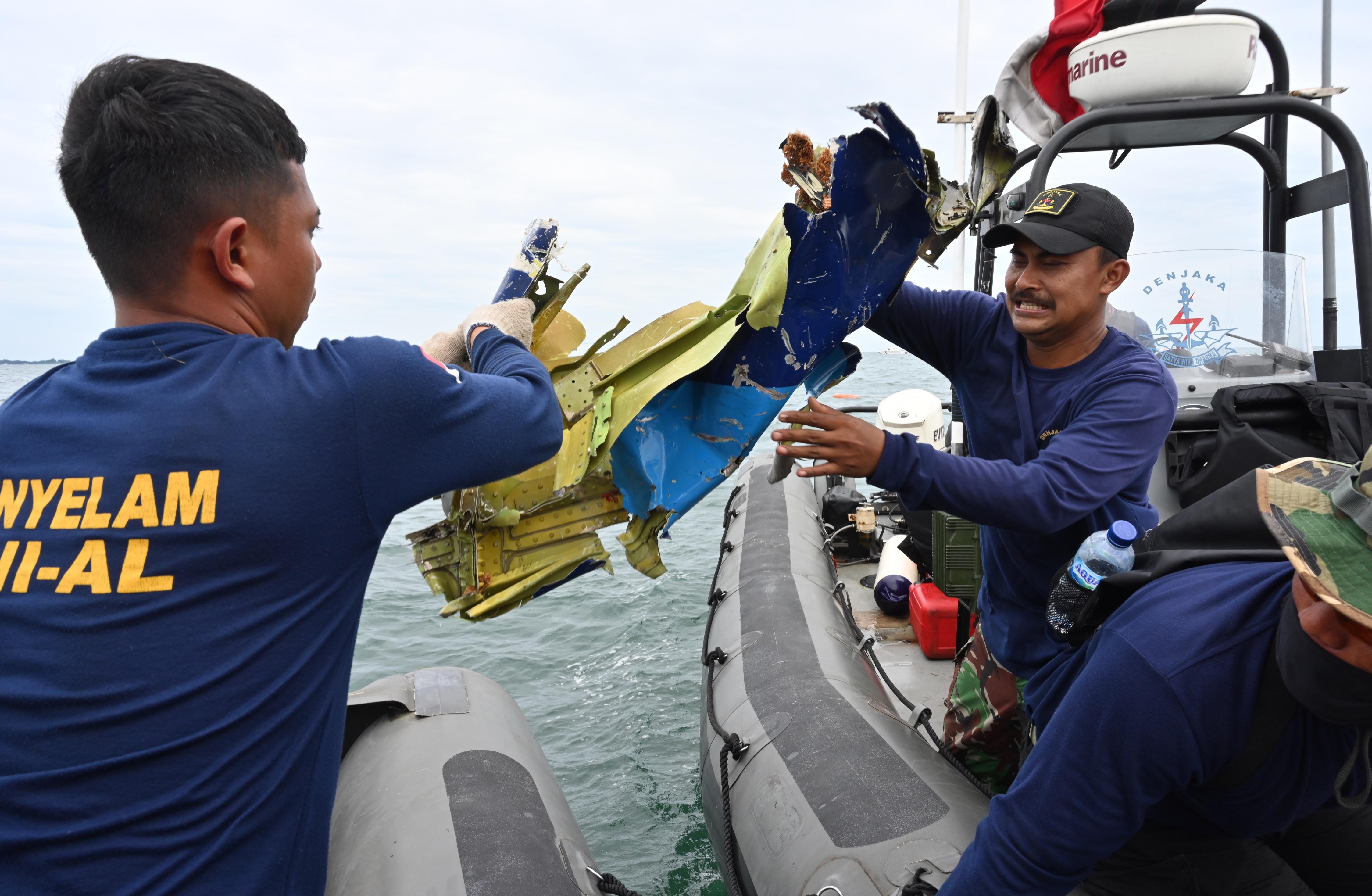 Regu penyelam TNI AL memindahkan benda yang ditemukan di Pulau Lancang. Foto: Adek Berry/AFP