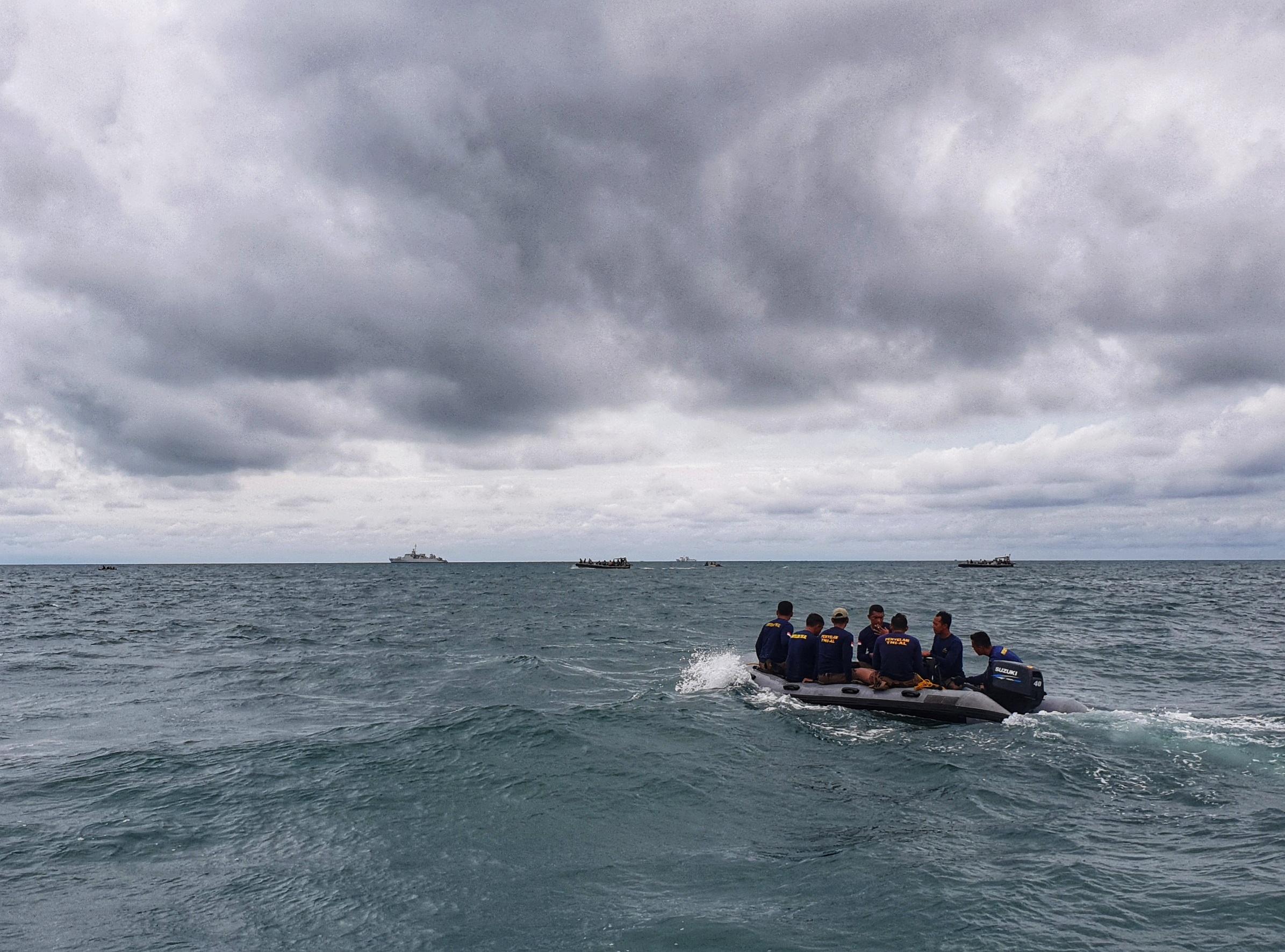 Regu penyelam TNI AL menuju lokasi pesawat jatuh pada 12 Januari 2020. Foto: Azwar Ipank/AFP