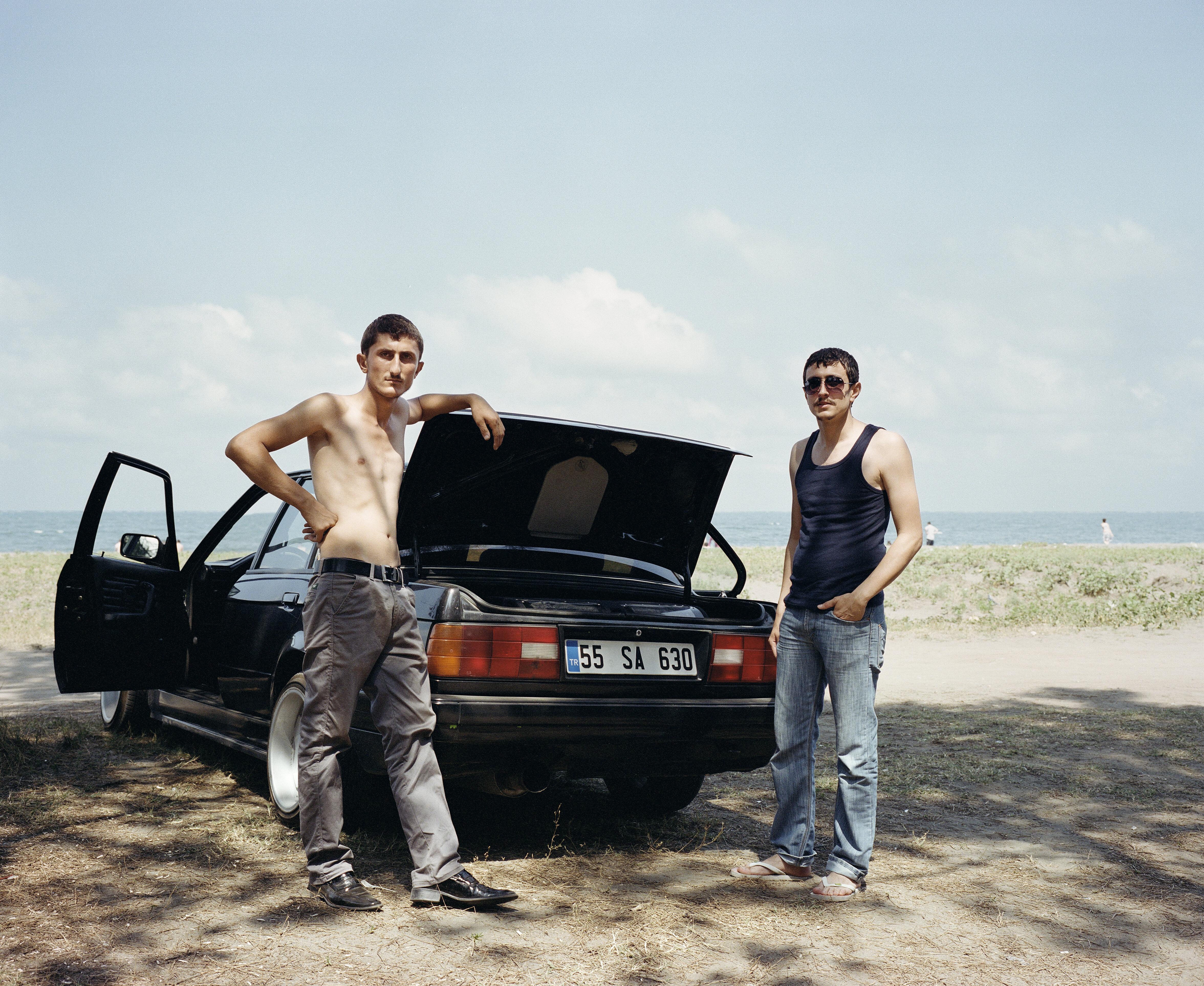 Dua laki-laki berpose di depan bagasi mobil.
