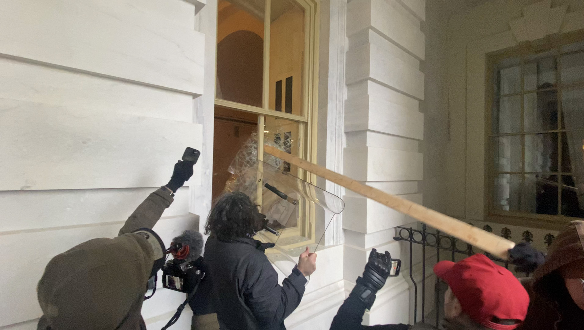 Pezzola using a riot shield to smash a Capitol Hill window. (Photo via Brendan Gutenschwager)