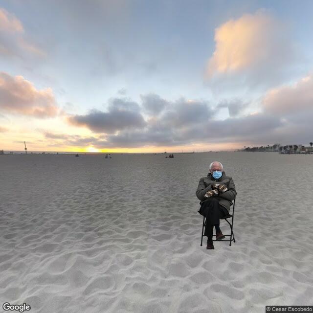 Bernie Sanders sitting on the beach.