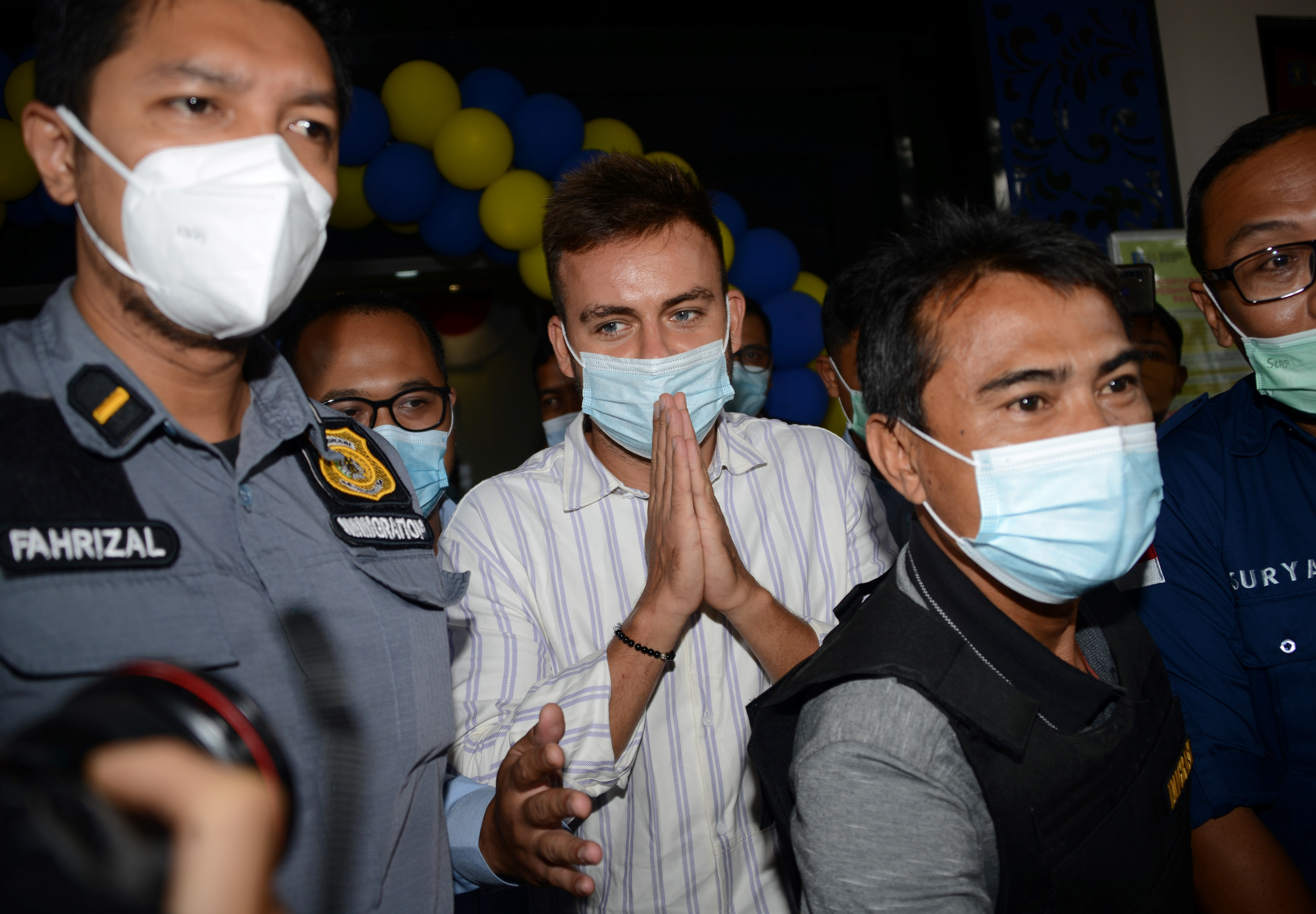 Russian national Sergey Kosenko is escorted by Indonesian immigration officials to Bali's Ngurah Rai Airport (PHOTO: AFP / SONNY TUMBELAKA)
