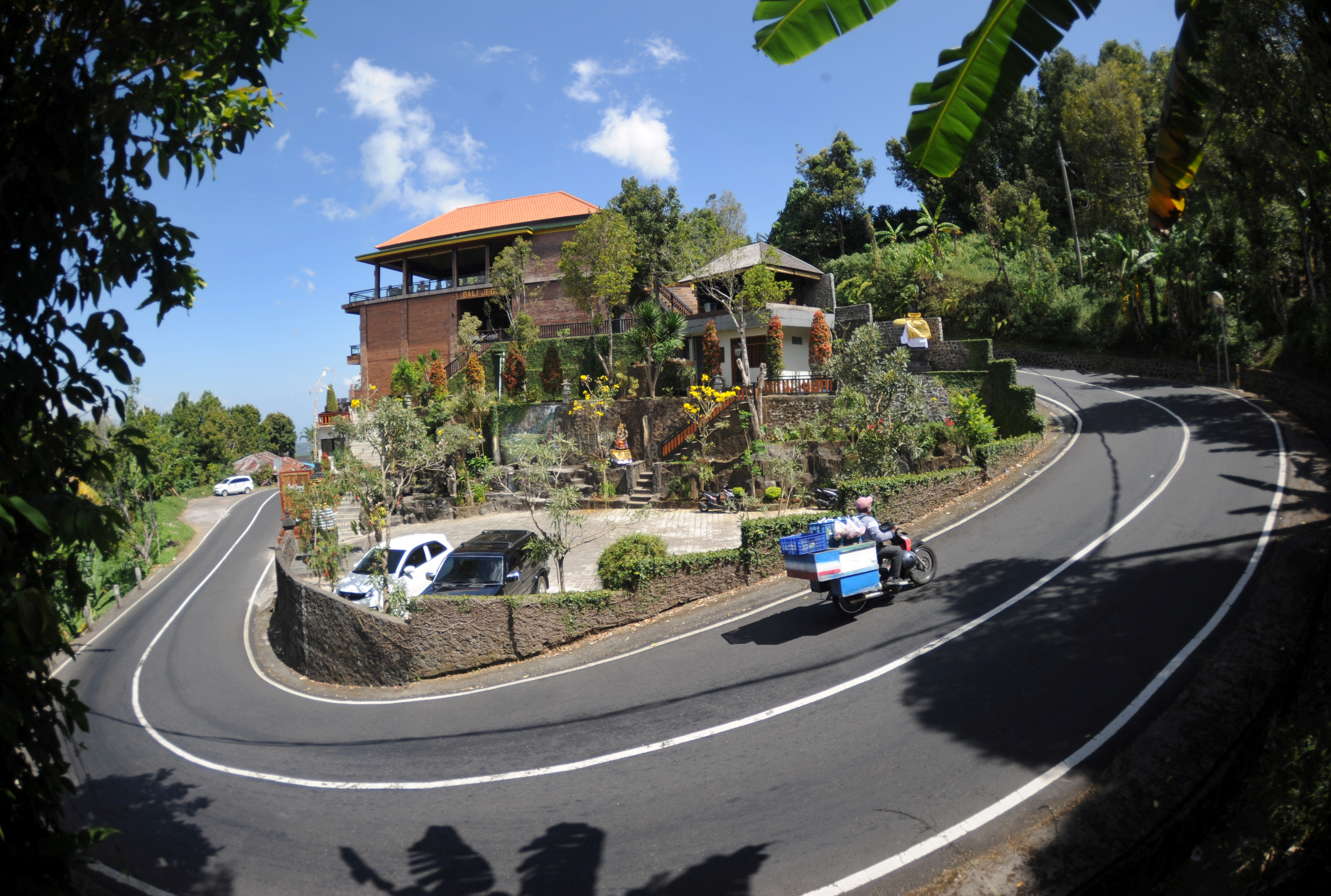 A motorist commutes past a villa in Bali's Munduk village, which has seen a downturn in tourists due to ongoing COVID-19 travel restrictions (PHOTO: AFP / SONNY TUMBELAKA)
