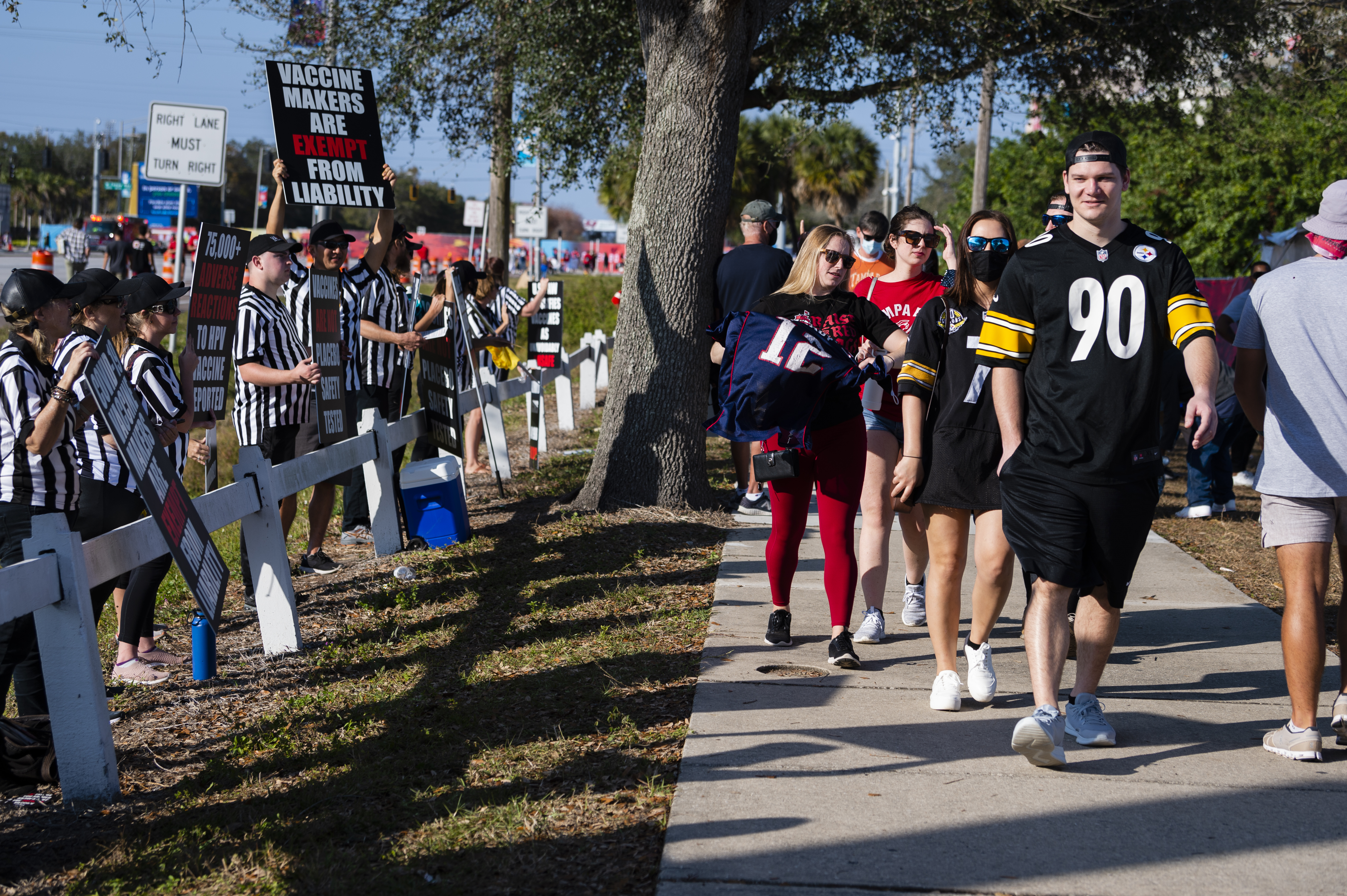 Fans pass by a protest against Covid-19 vaccine outside the Raymond James Stadium ahead of the Super Bowl LV game between Tampa Bay Buccaneers and Kansas City Chiefs in Tampa, Florida, United States on February 07, 2021.