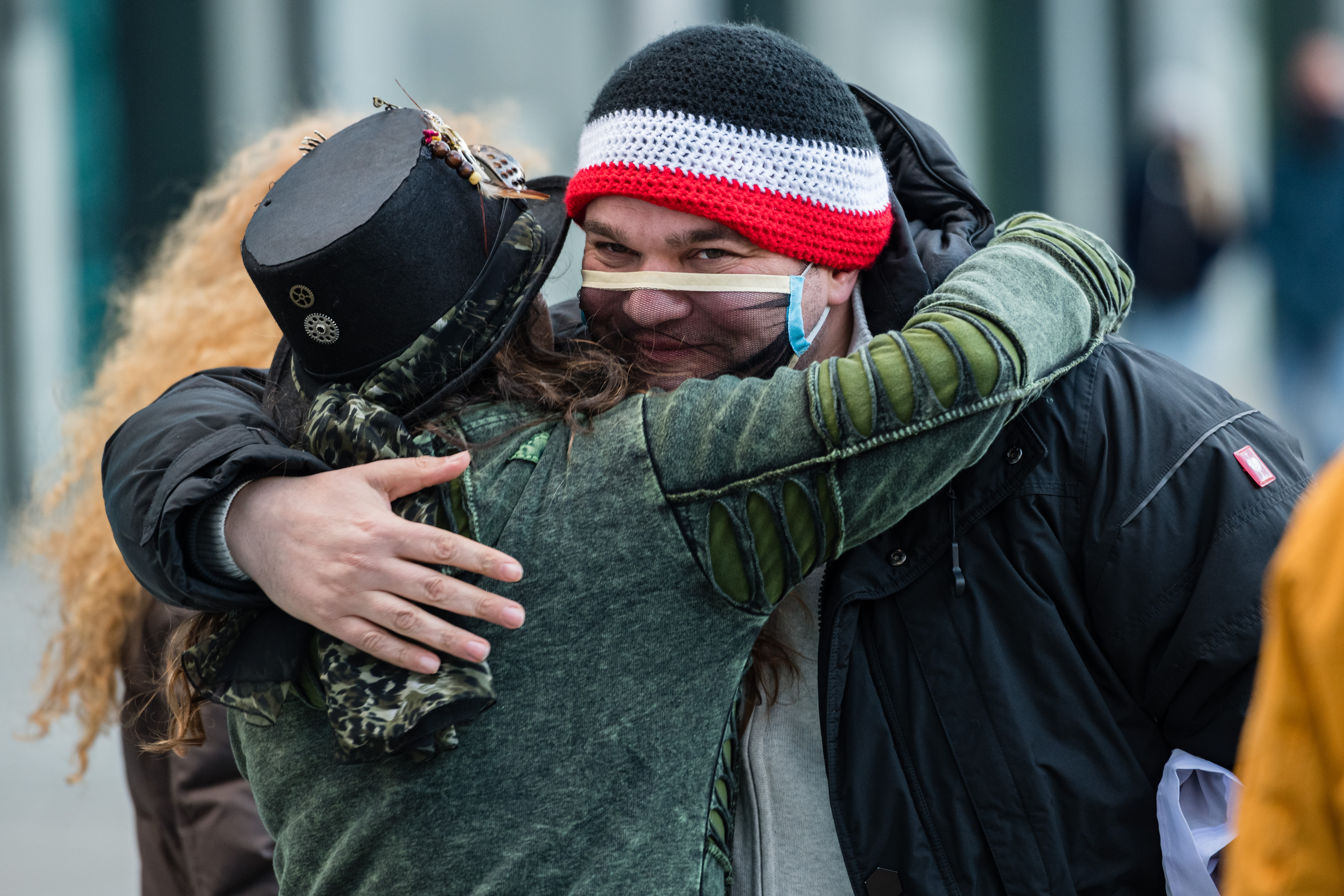 Two maskless protesters embrace in Leipzig in November last year. Photo: Stringer/Getty Images