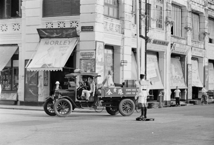 Truk lewat di depan polantas yang memakai papan sinyal semafor di bahunya. Foto diambil di era 1940-an.