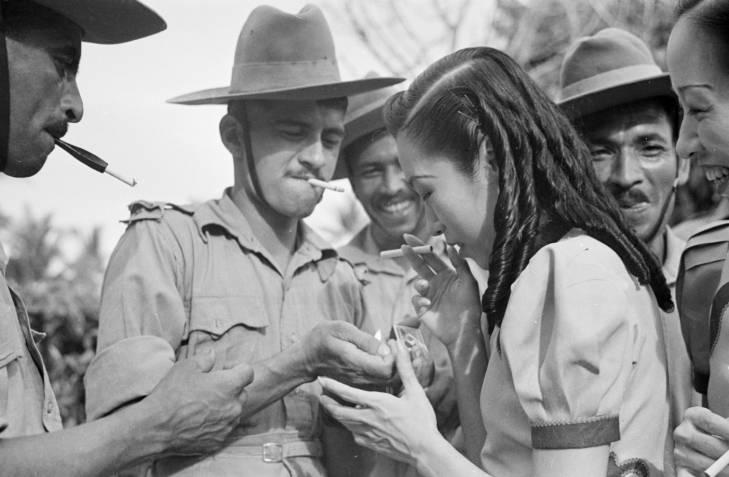 Lelaki berseragam menyalakan rokok seorang perempuan pada 1941. Ketiga lelaki itu kemungkinan anggota korps rumah sakit India.