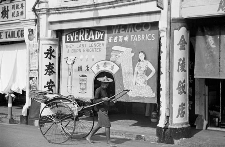 Becak lewat di depan toko.