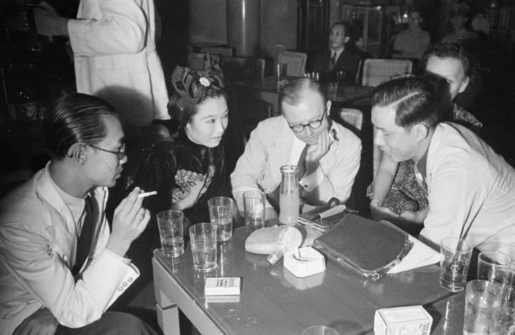 Lima orang mengobrol di meja kelab malam pada 1940-an.