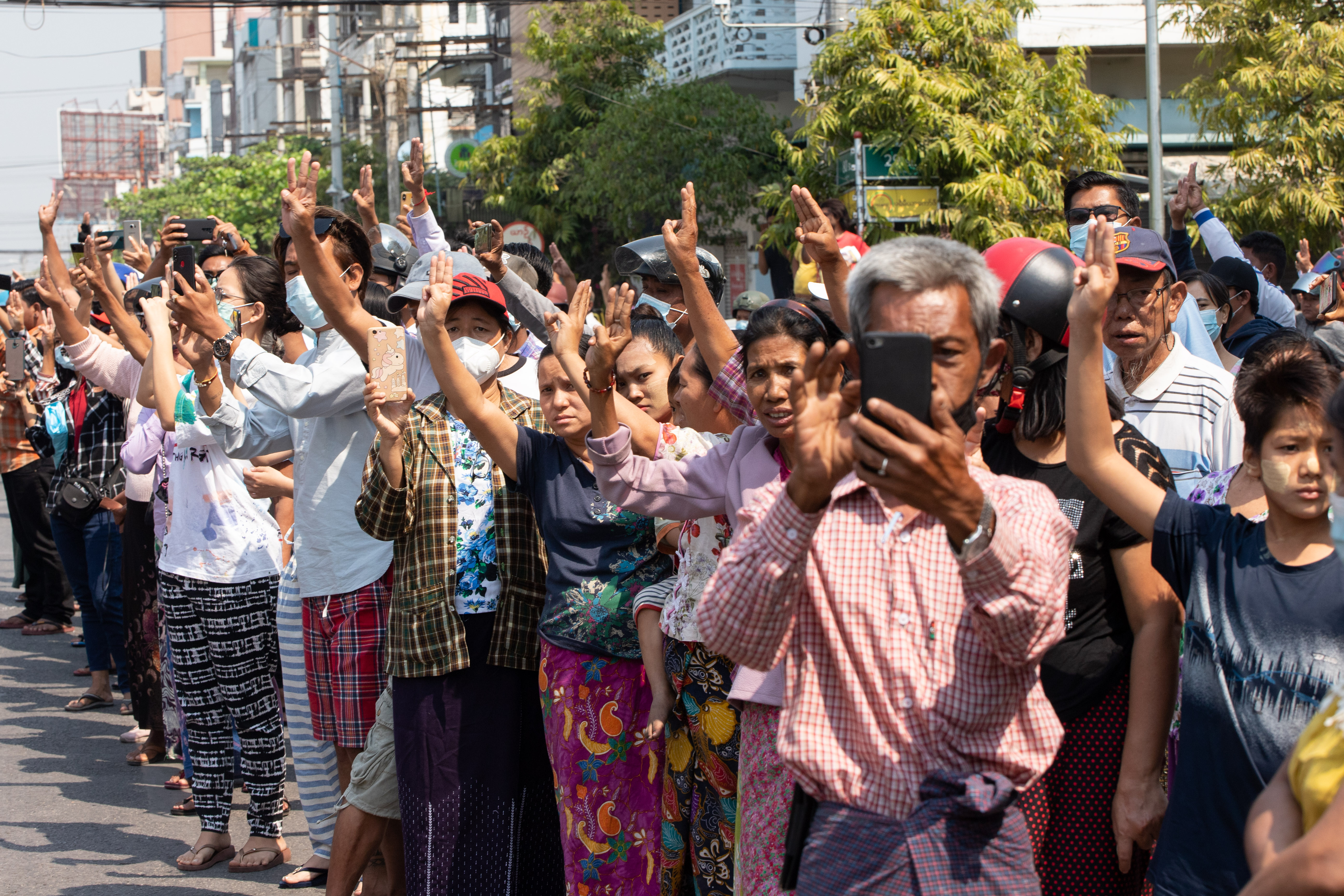 Crowds of supporters flash the three finger salute as a tribute to young protester Angel. PHOTO: STRINGER