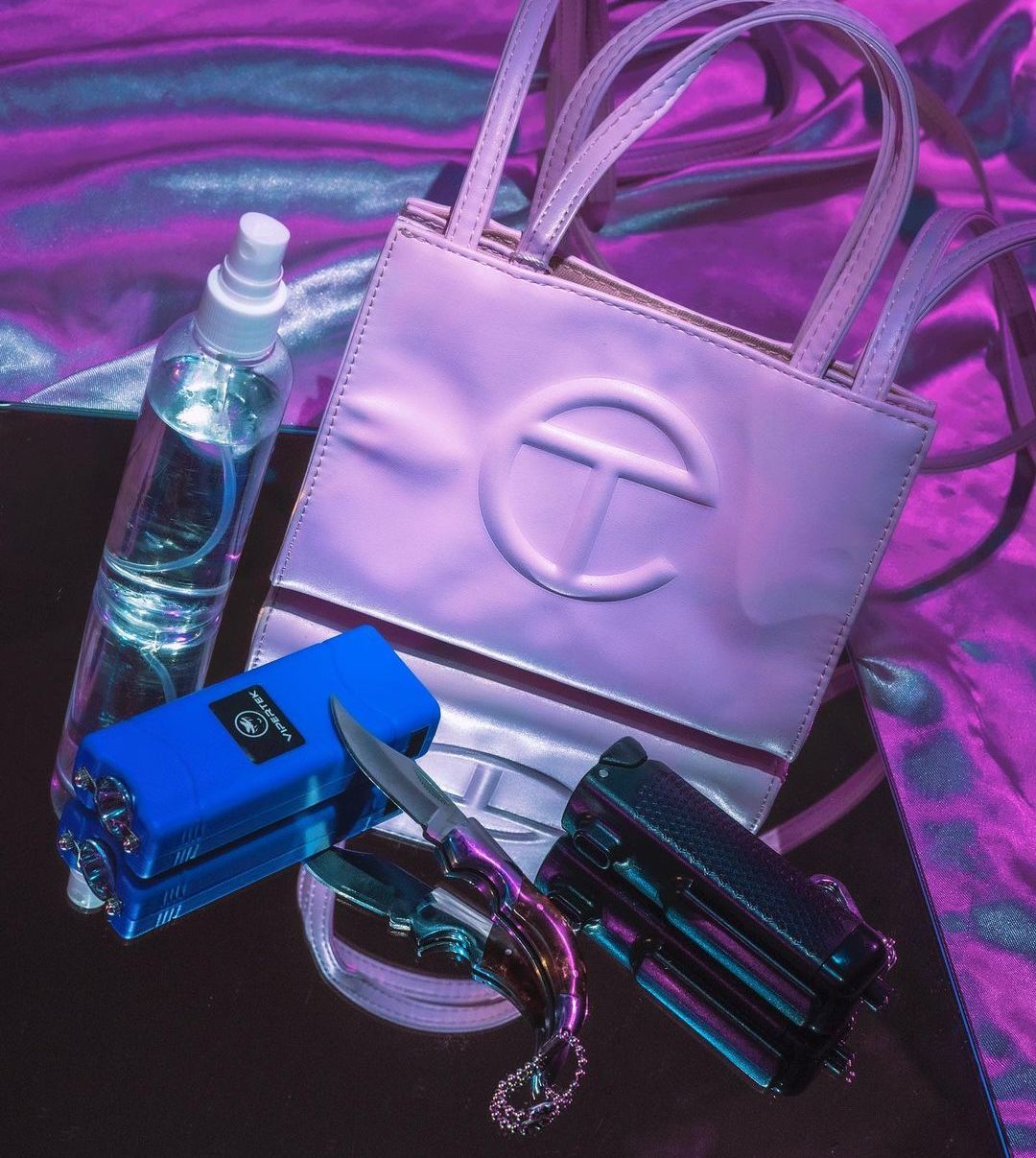 Self-defense items sit on a reflective table in front of a pink and blue background, including a bottle of pepper spray, a stun gun, a switchblade, and a white Telfar tote bag.