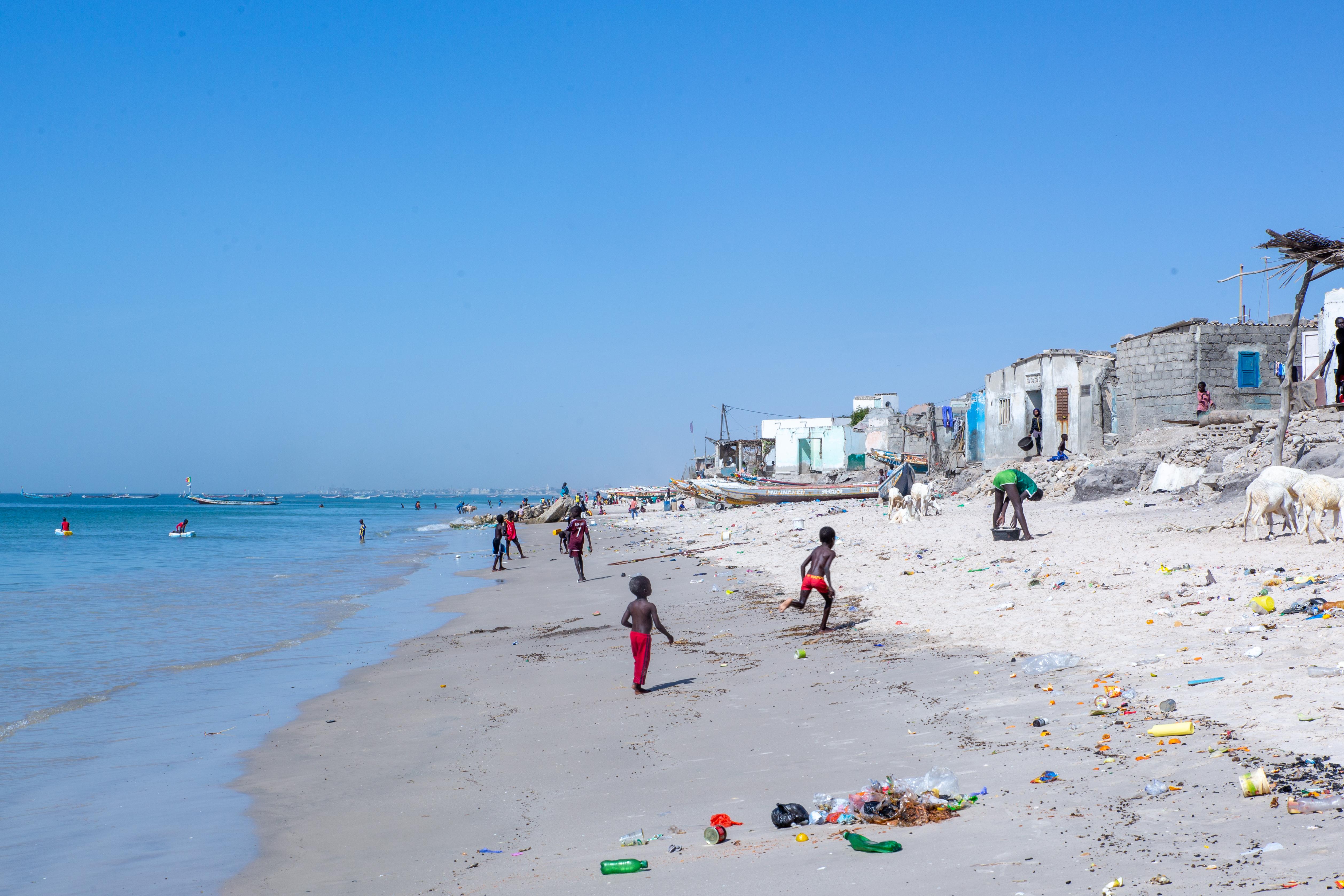 Children play on a beach in Senegal near several homes.