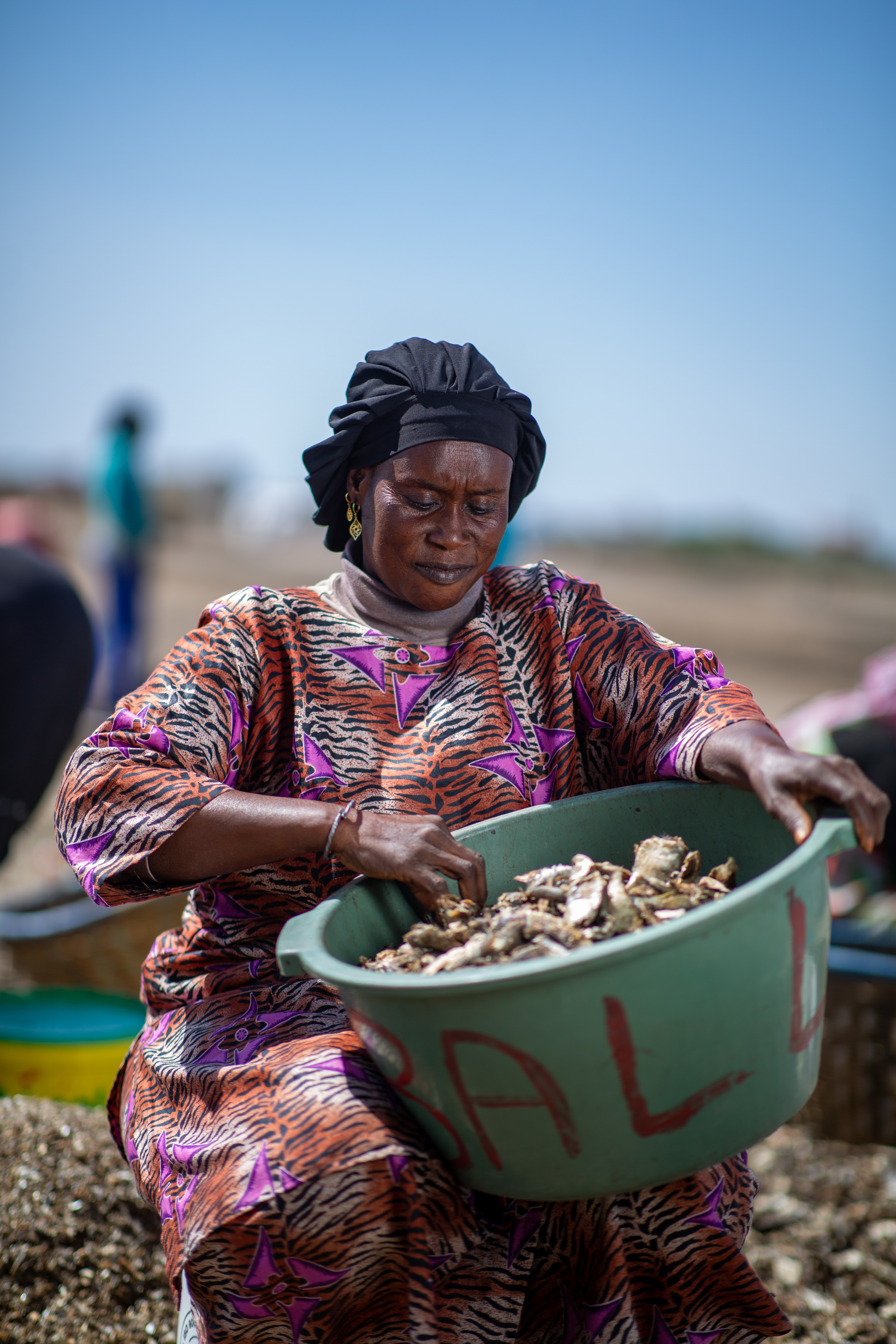 A woman sorts fish from a bucket.