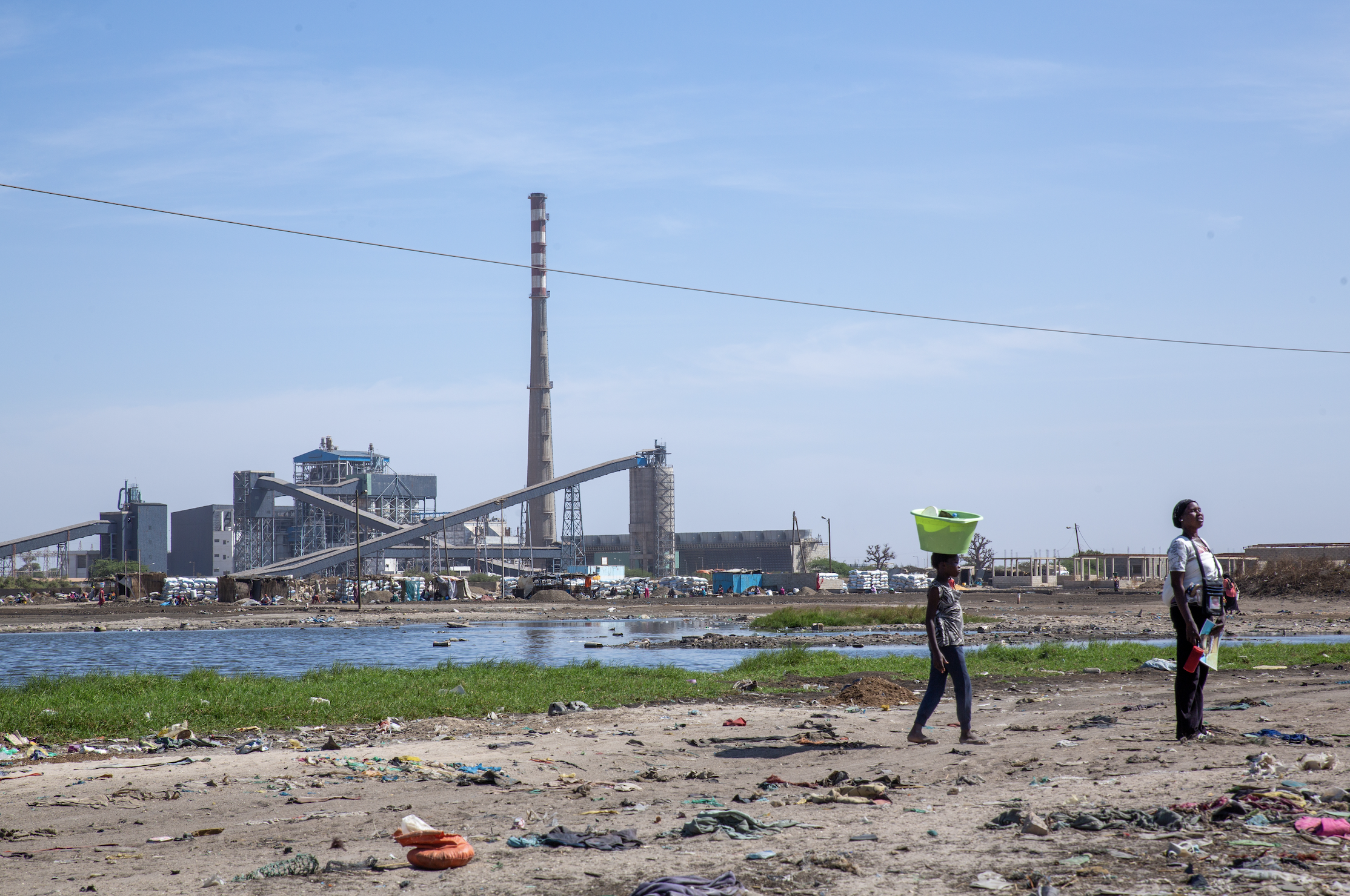 Two people stand on a road next to the Sendou plant in Bargny.
