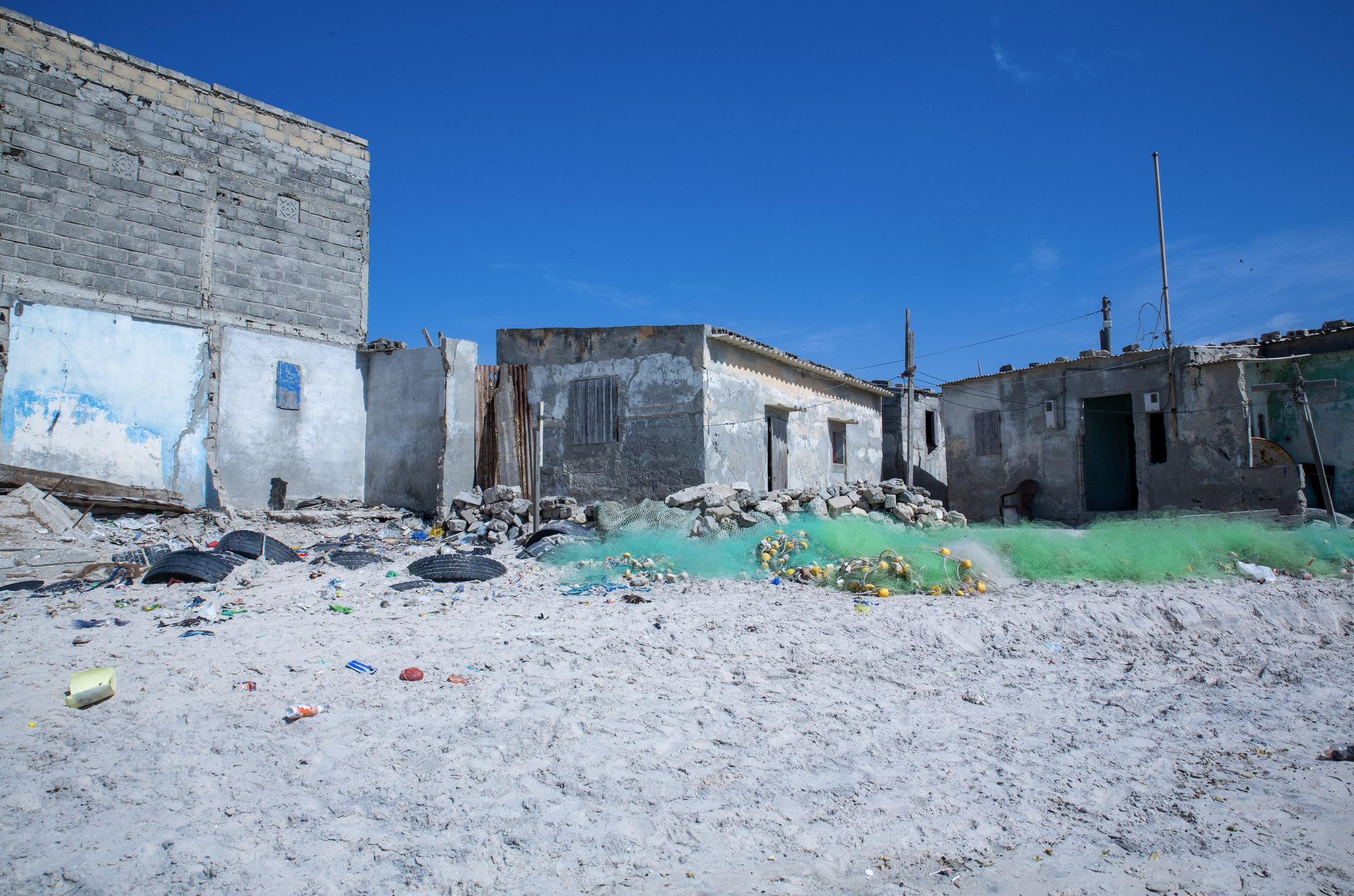 Fishing nets piled on the sand sit next to homes in Bargny.