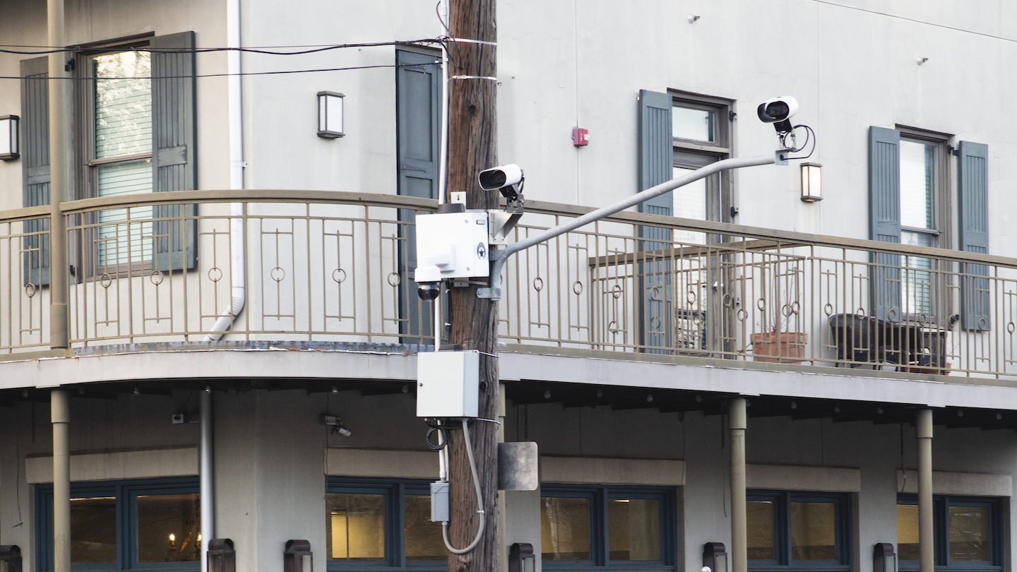 Surveillance cameras hang from a metal pole on a street corner in New Orleans.