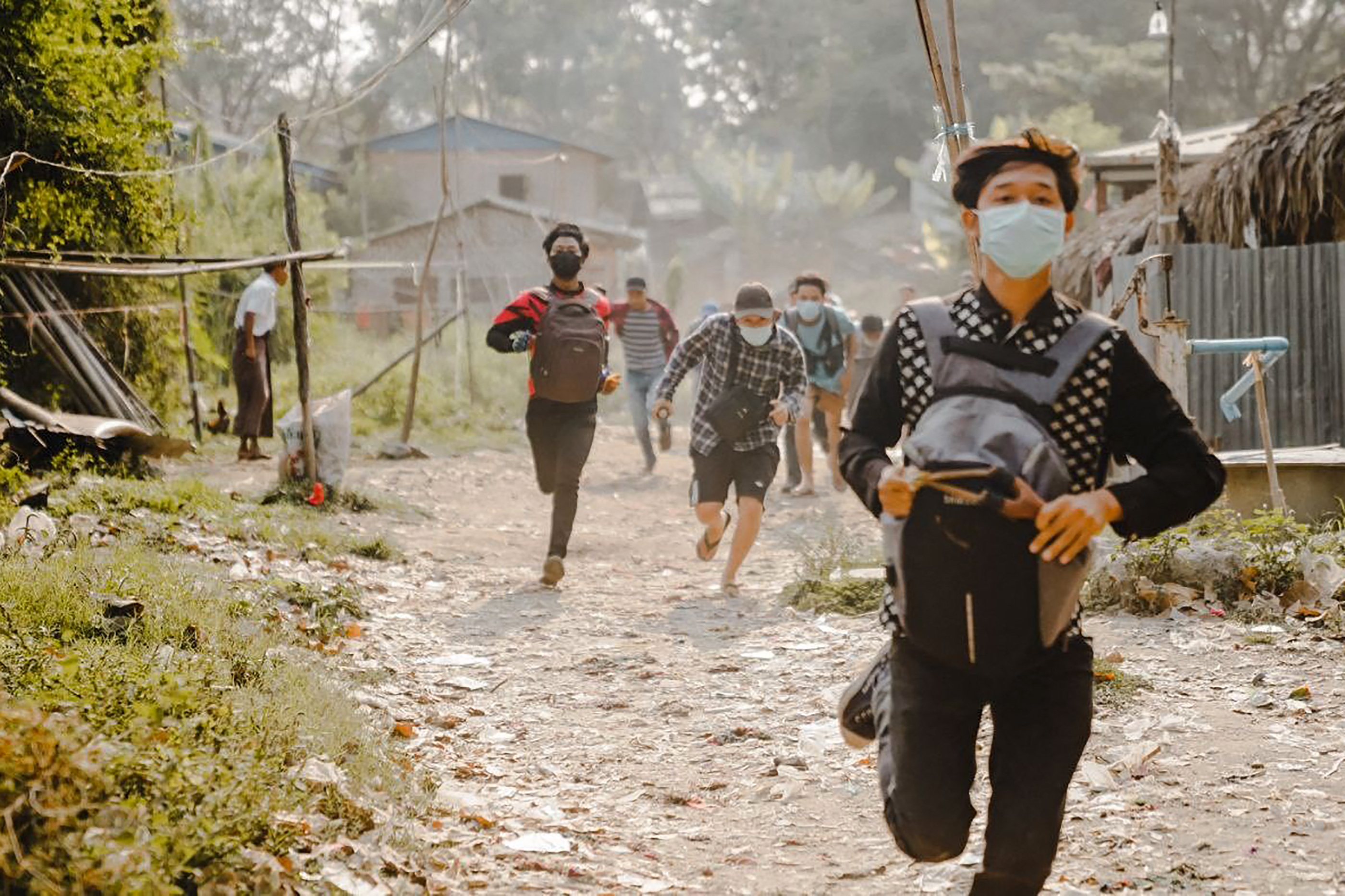 Protesters fleeing armed forces in Mandalay. PHOTO: AFP