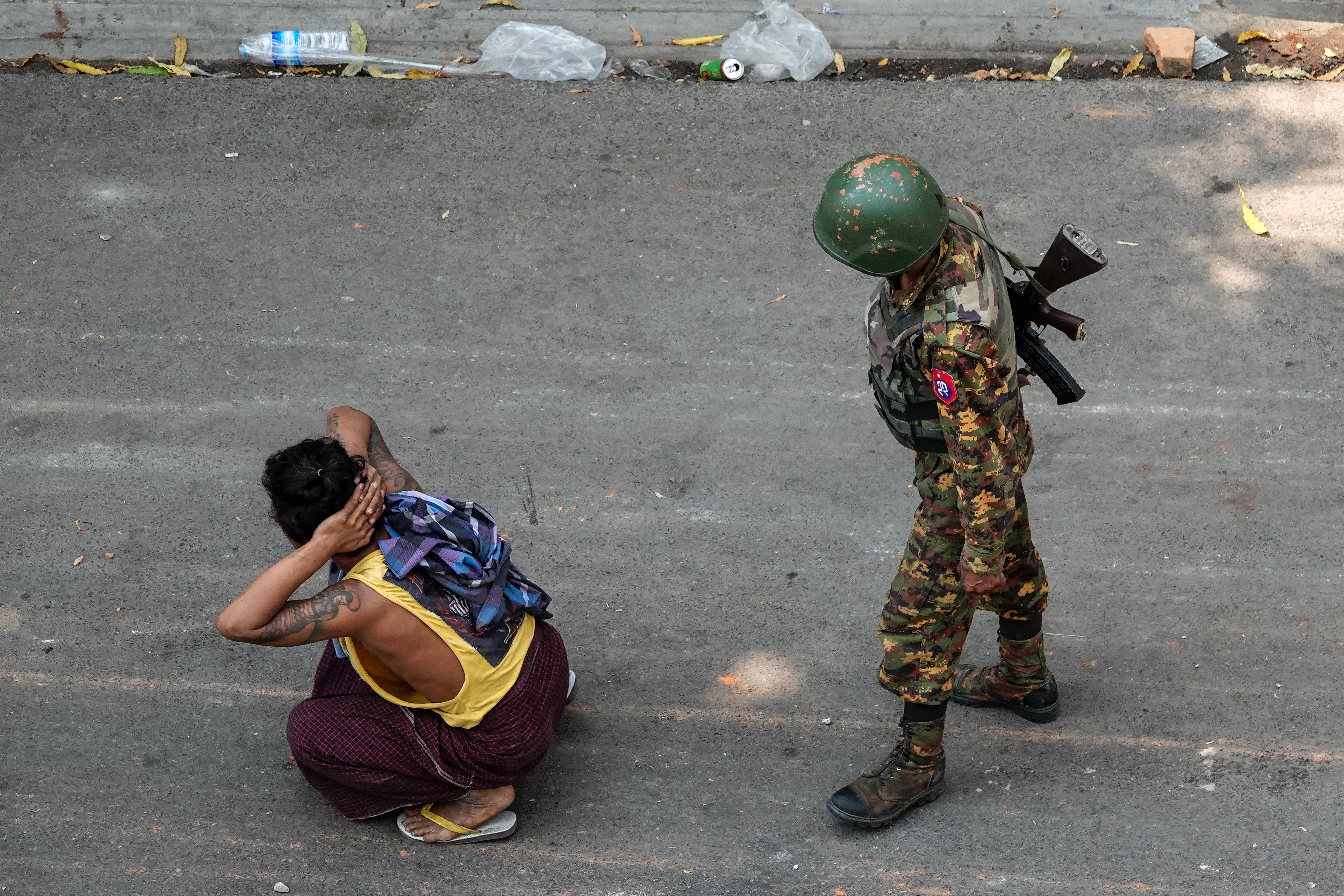 A soldier stands next to a detained man during a demonstration against the military coup in Mandalay. PHOTO: AFP