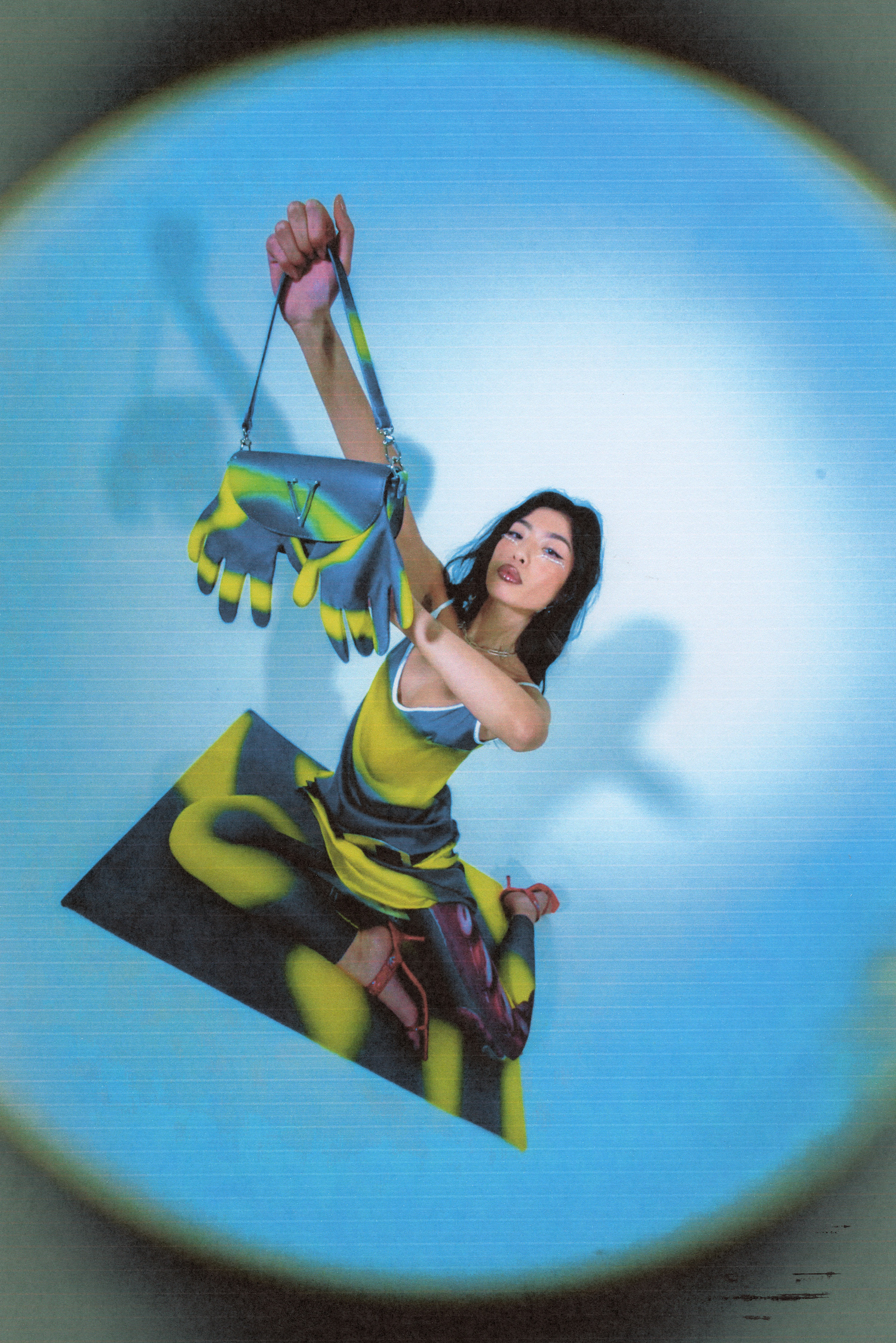 A woman wearing a tie-dye spaghetti strap dress and leggings by Vivendii, holding a Vivendii baguette bag up to the camera
