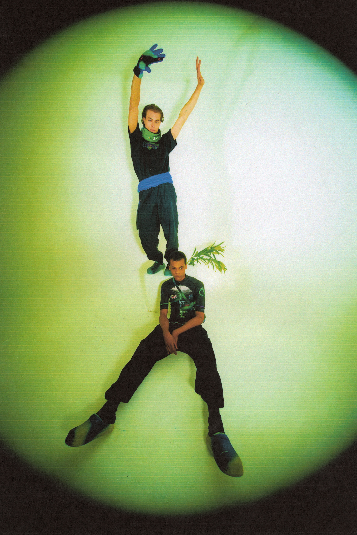 Two men wearing full Vivendii looks shot through fish-eye lens. One is sat on the floor, the other stood on a cube behind him.