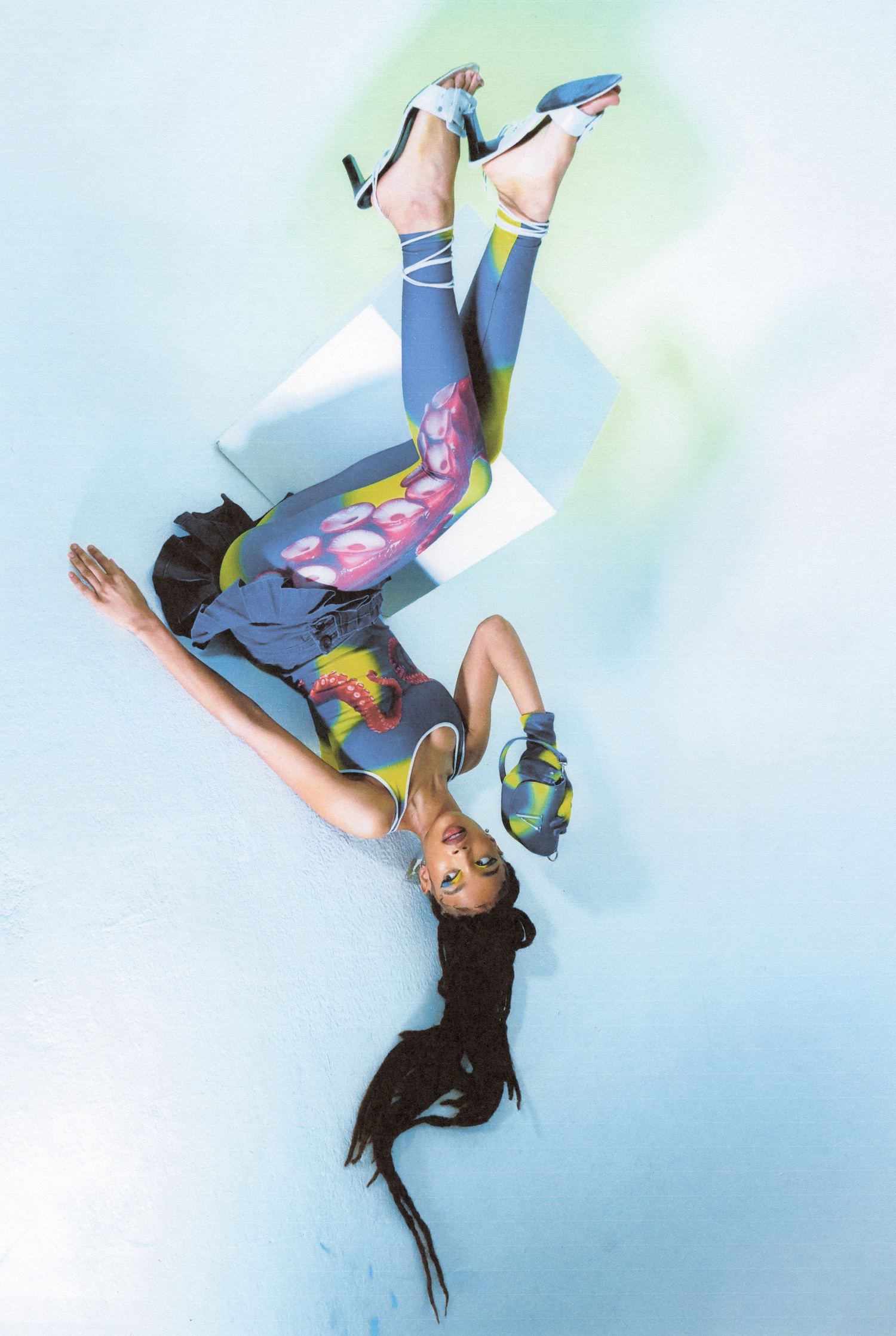 A woman wearing a full Vivendii look lying on her back with her legs propped on a stool. The angle of the images makes it seem as if she is hanging upside down.