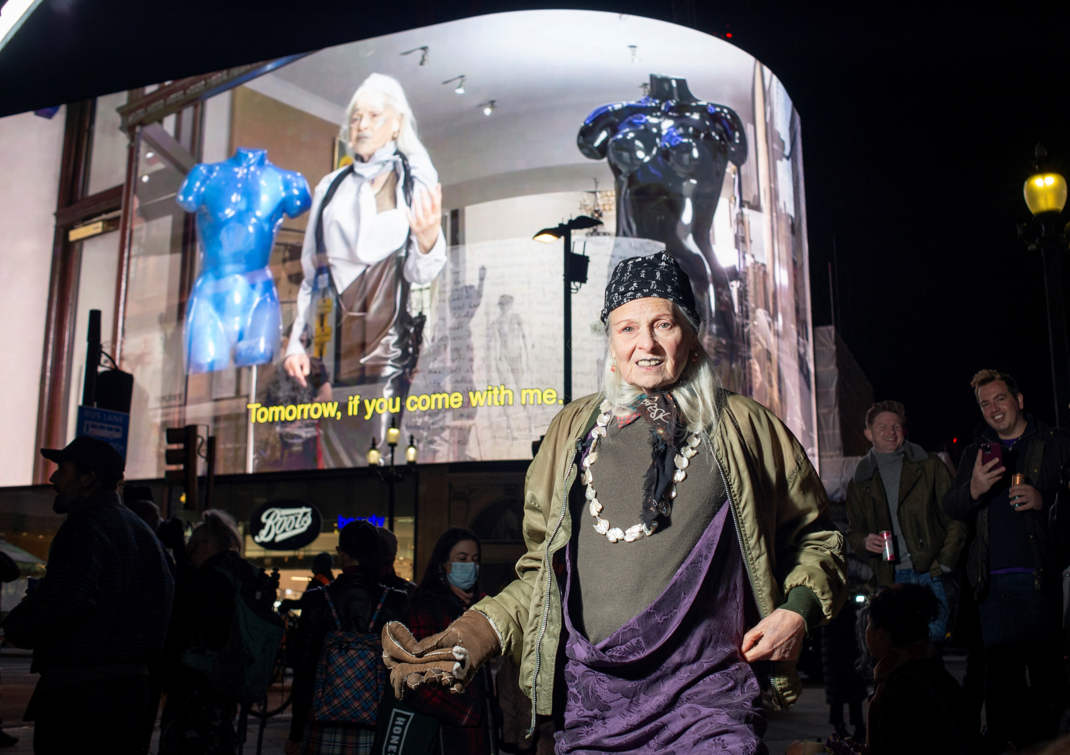 Vivienne Westwood stood in front of the Piccadilly Circus lights on her 80th birthday. Behind her, a video of her performing a reading plays.