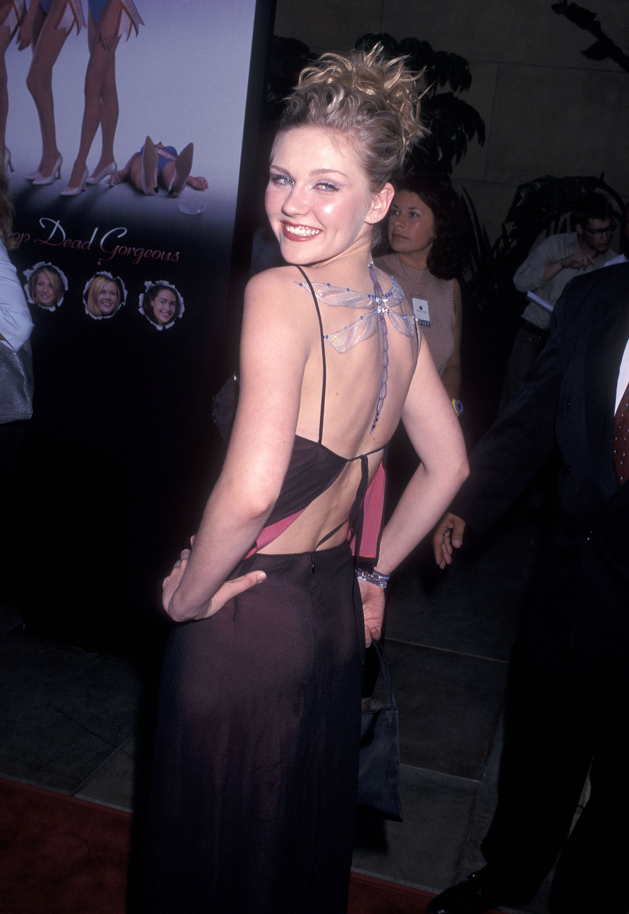 kirsten dunst on the red carpet in a backless dress and 90s dragonfly body art