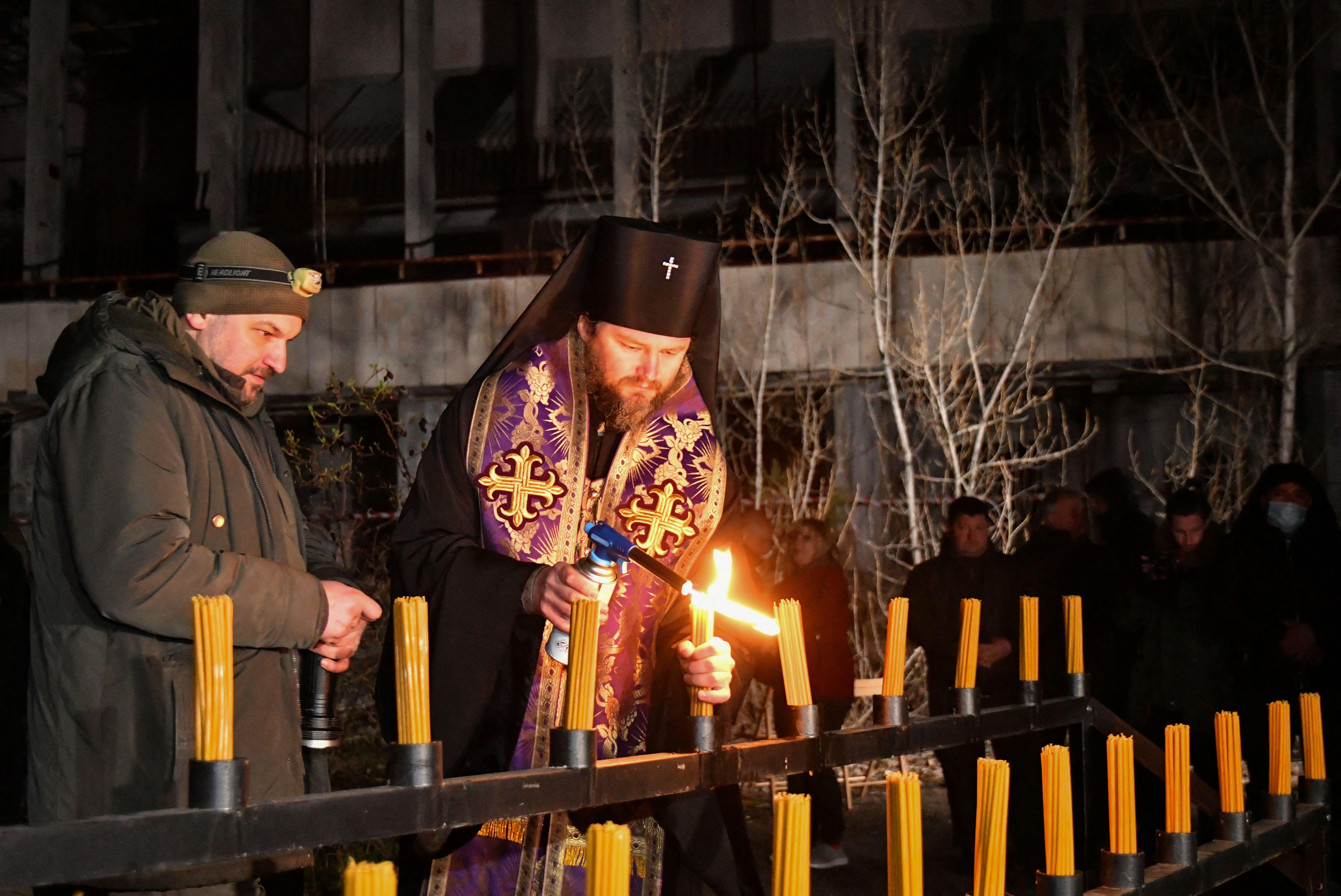 Pendeta ortodoks menyalakan lilin di alun-alun pusat kota Pripyat, tak jauh dari Pembangkit Listrik Tenaga Nuklir Chernobyl, pada 26 April 2021. Mereka mengadakan acara peringatan 35 tahun bencana Chernobyl. Foto: Genya Savilov/AFP