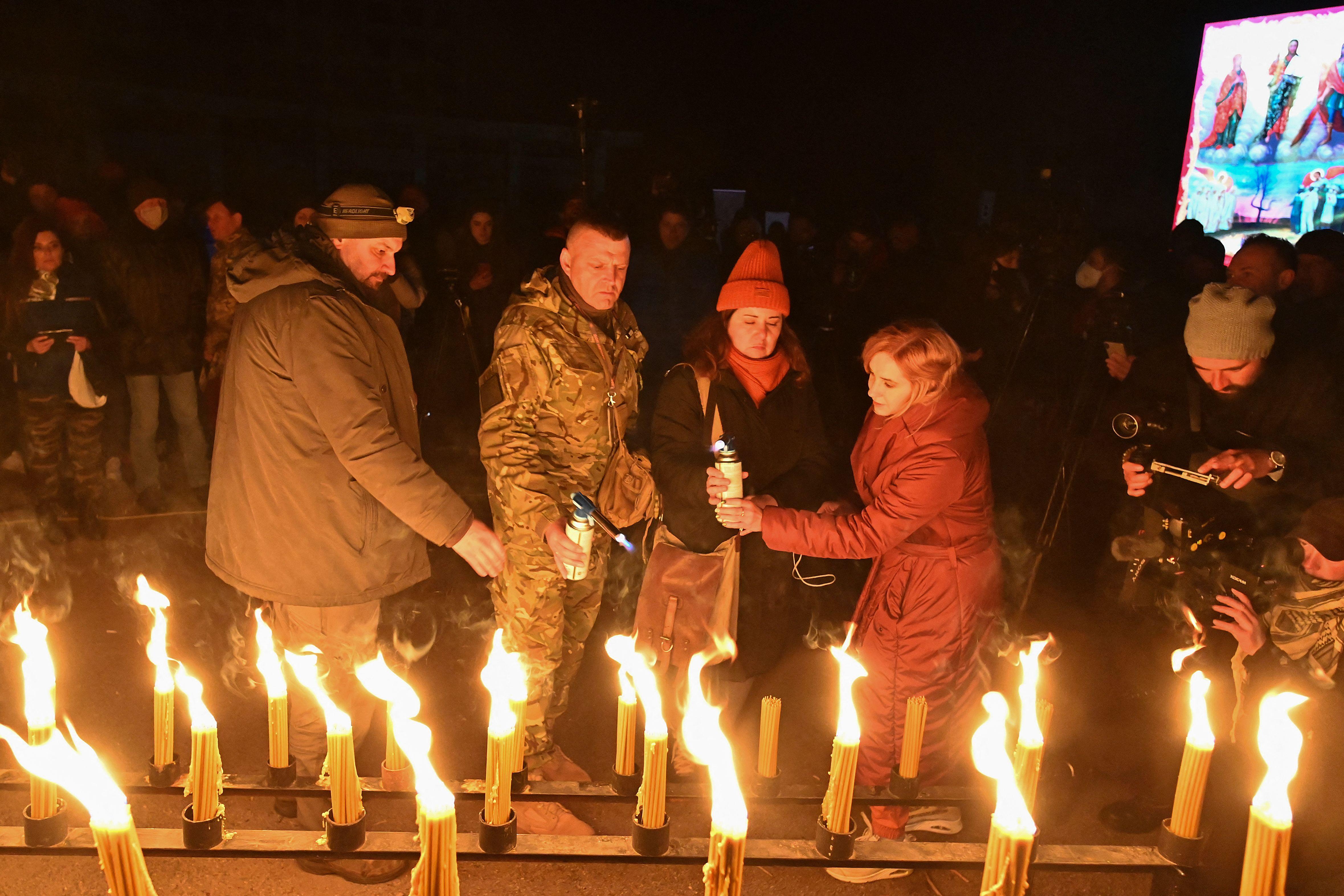Warga menyalakan lilin di alun-alun pusat kota Pripyat. Foto: Genya Savilov/AFP