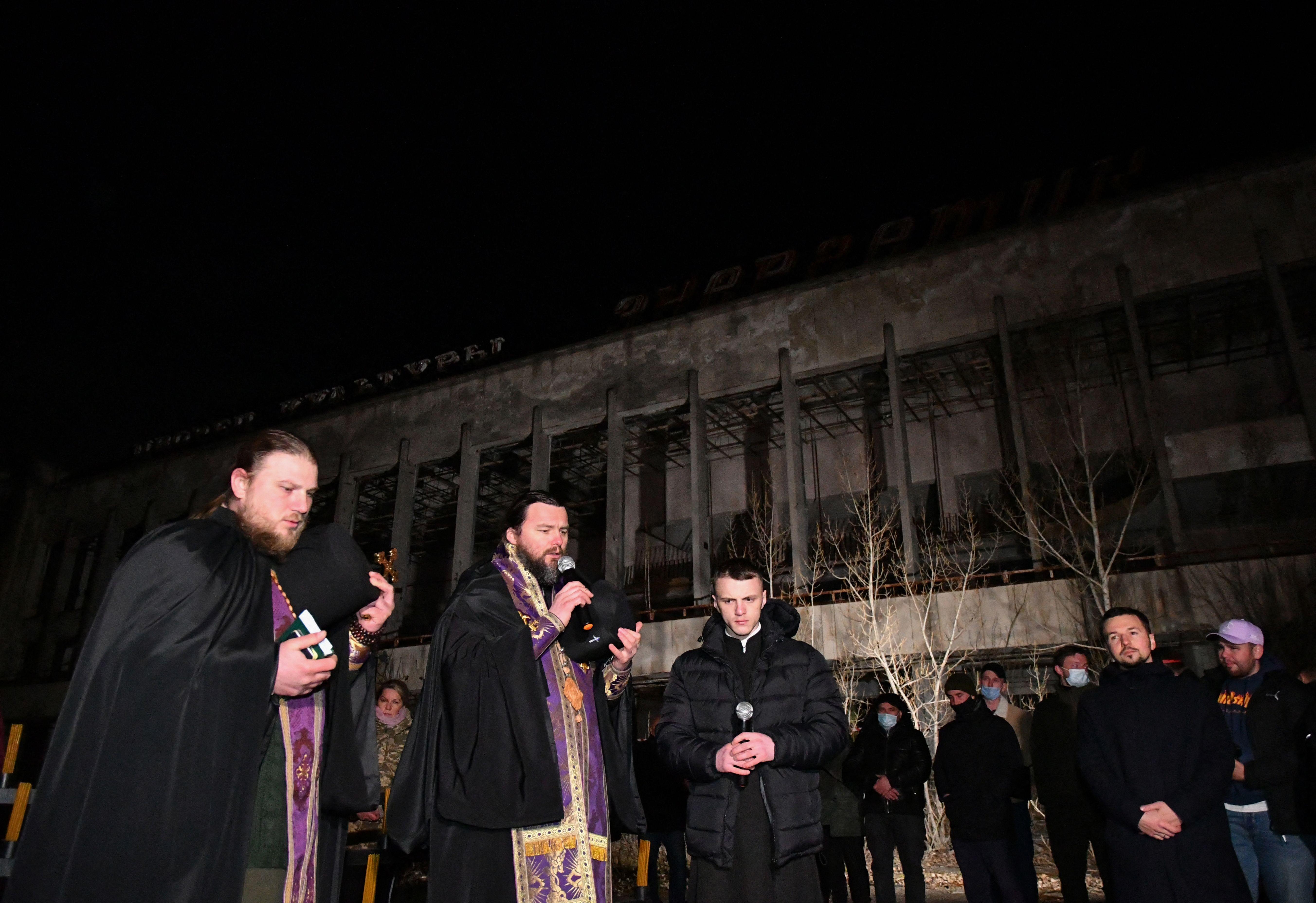 Pendeta ortodoks memimpin doa untuk korban tewas Chernobyl di alun-alun pusat kota Pripyat. Foto: Genya Savilov/AFP