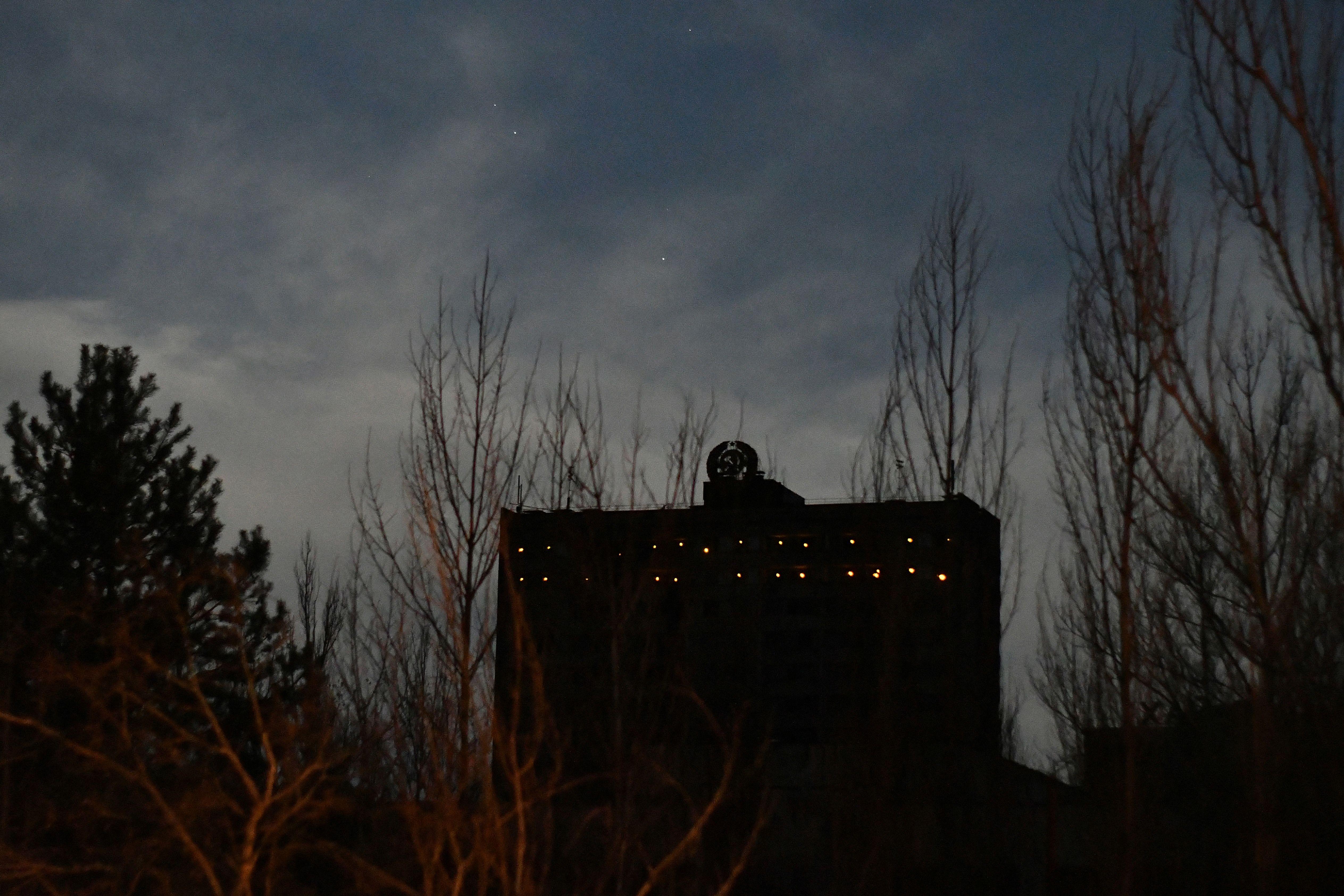 Cahaya lampu terpancar melalui jendela gedung terbengkalai di kota mati Pripyat. Foto: Genya Savilov/AFP