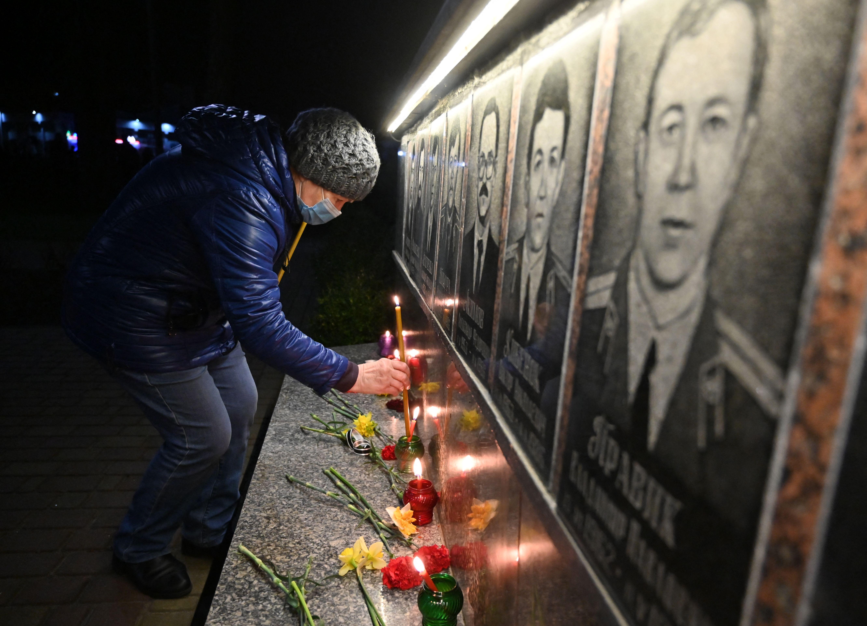 Perempuan menyalakan lilin dalam upacara peringatan yang diselenggarakan di Slavutych. Foto: Sergei Supinsky/AFP via Getty Images
