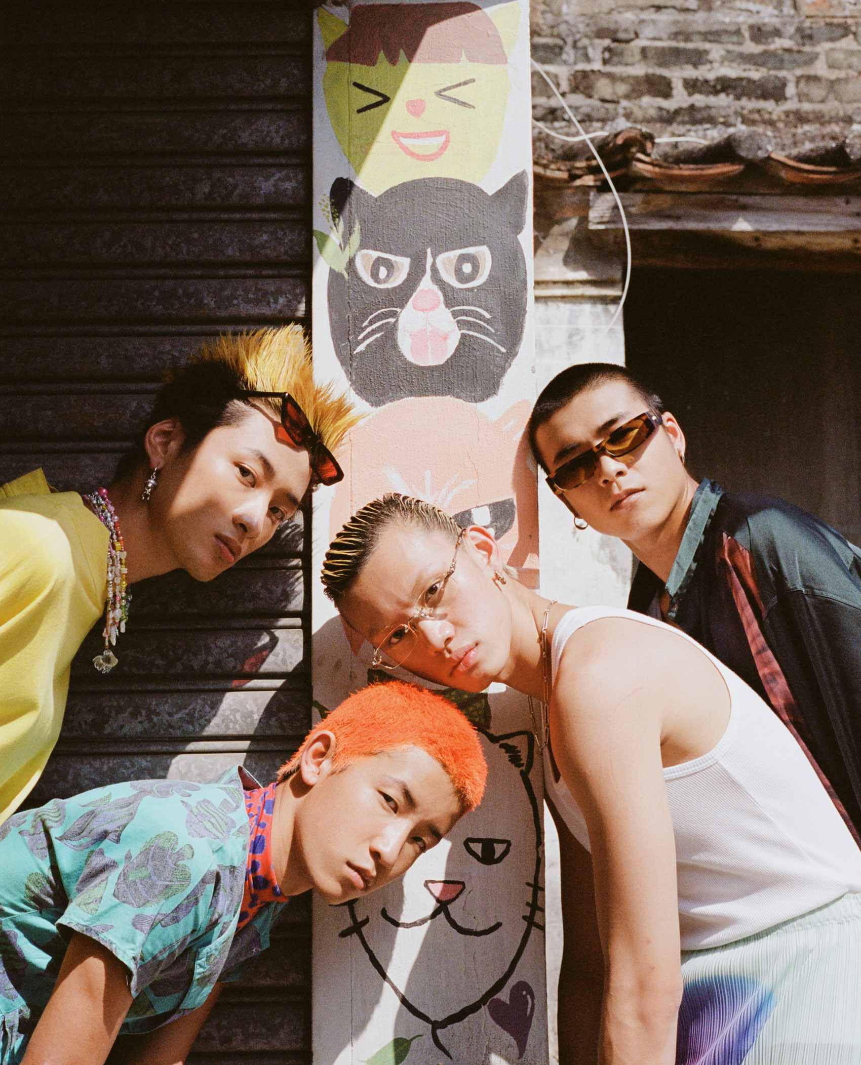 four young men with colourful hair lean into shot in front of a wall painted with a totem of cat heads