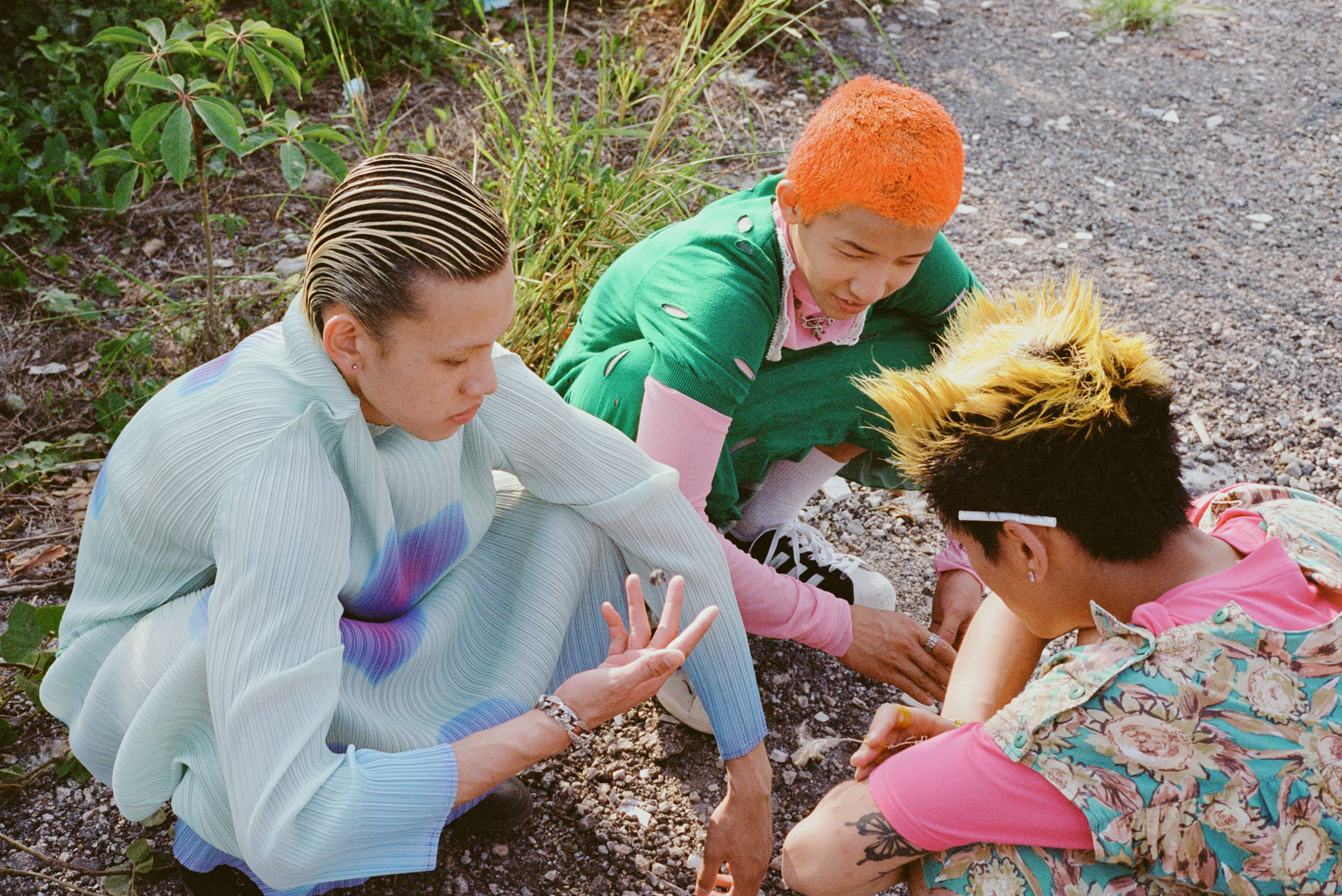 three young men with colourful hair wear bright dresses as they squat on a gravel floor, talking